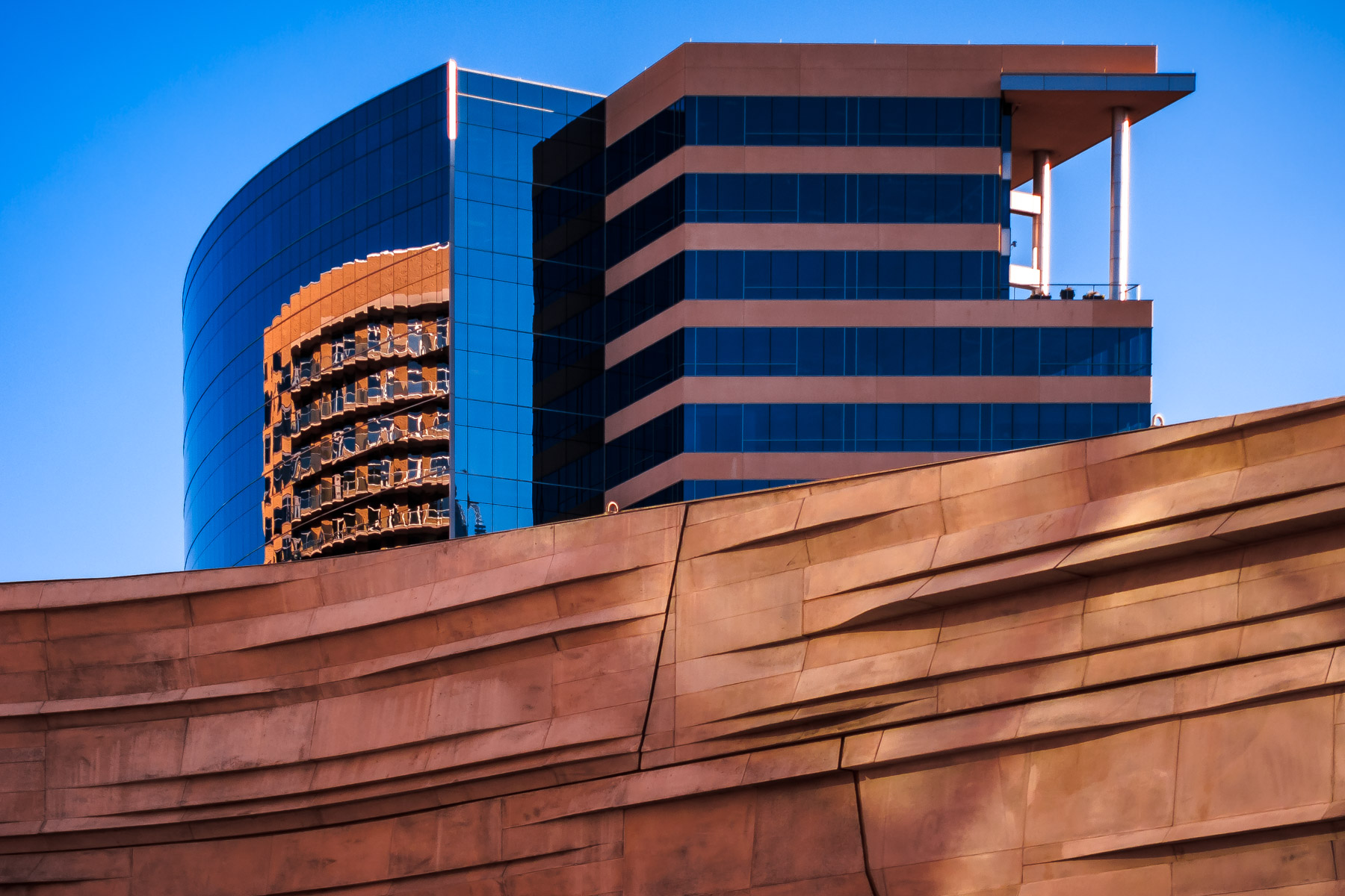 An adjacent building rises over a wall at Dallas' Perot Museum of Science & Nature.