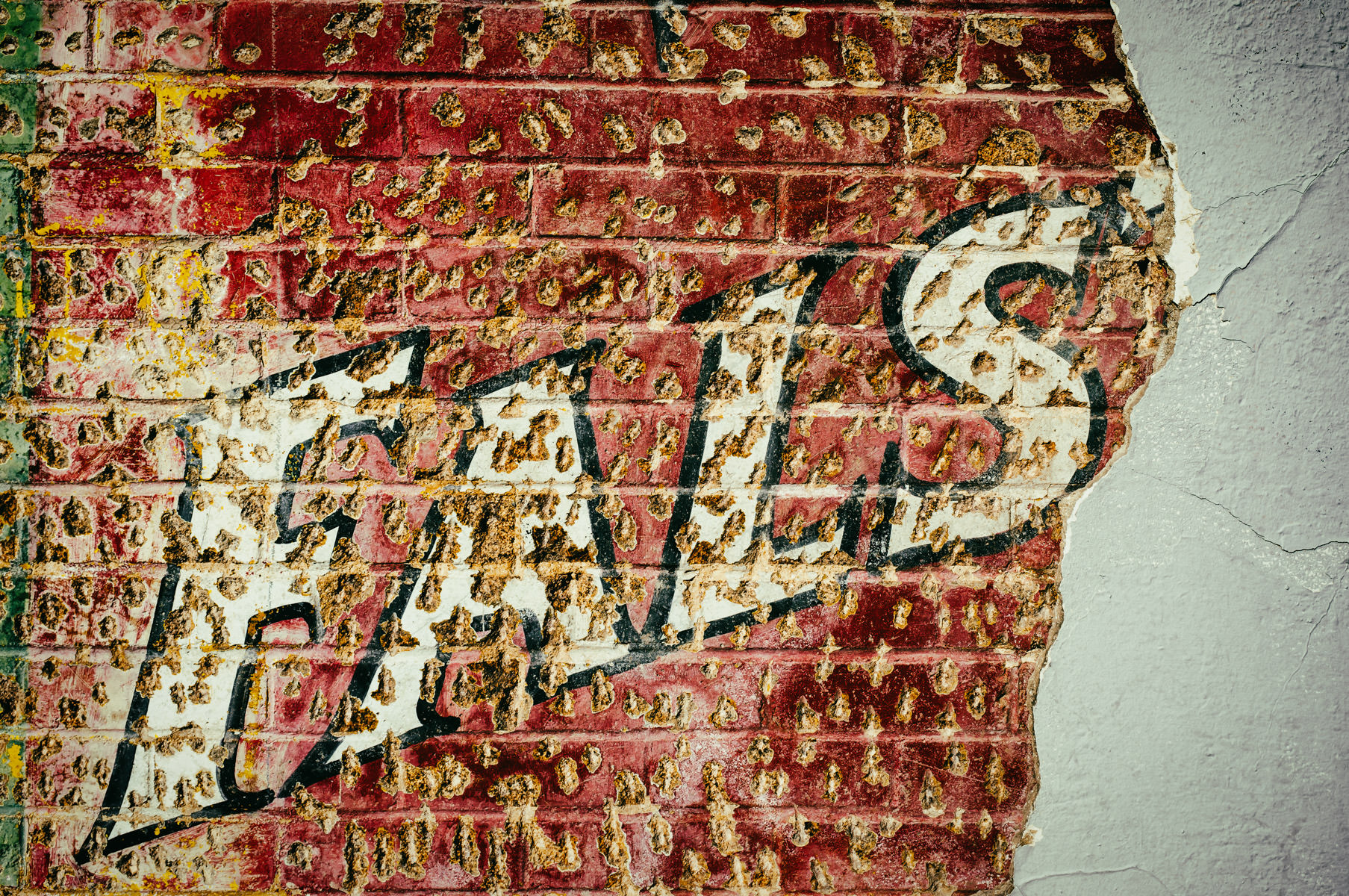 A plastered-over Falstaff beer advertisement on the side of a building in Fort Worth's Stockyards District.