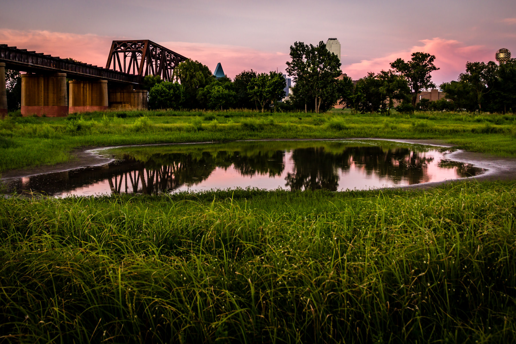 A railroad bridge over the Trinity River just west of Downtown Dallas, as seen just before sunset.