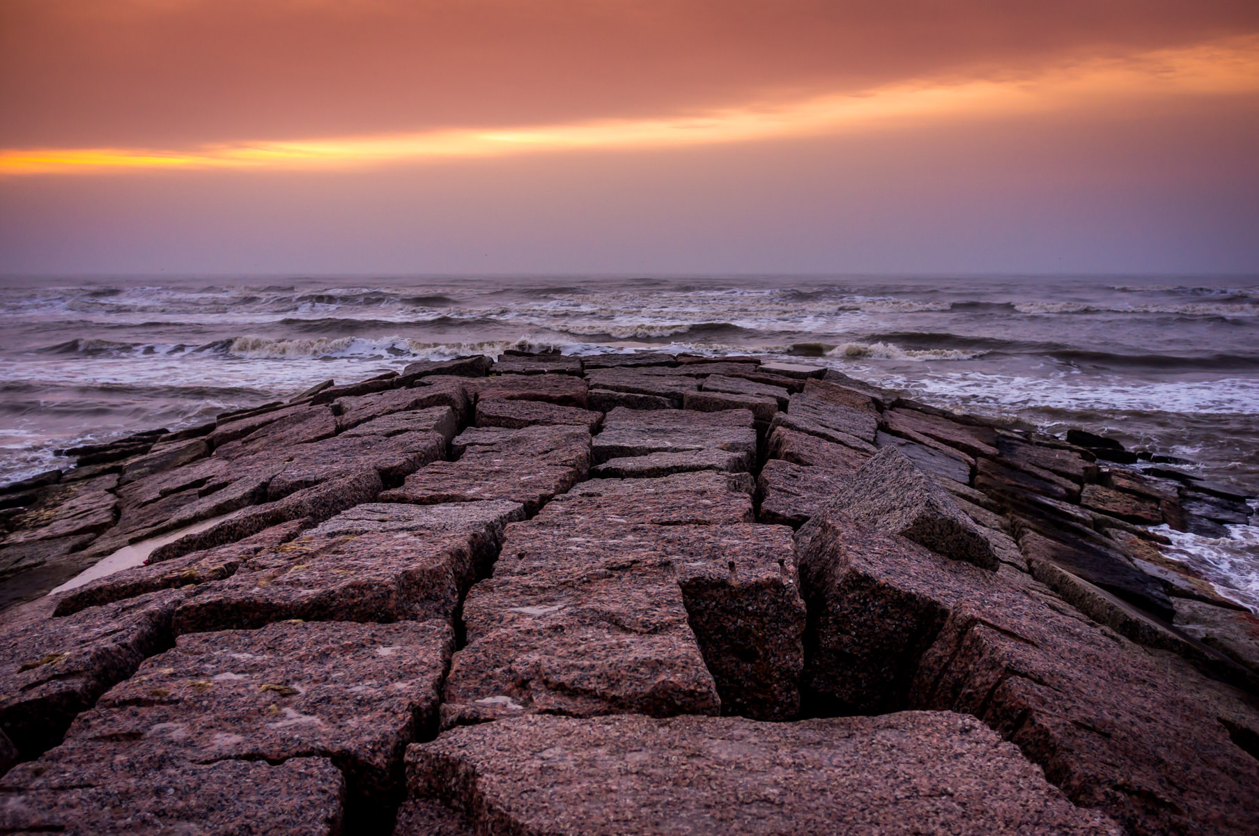 Texas pink granite forms a jetty or, more-accurately, a groyne, jutting out into the early-morning sun-painted Gulf of Mexico from Galveston Island, Texas.