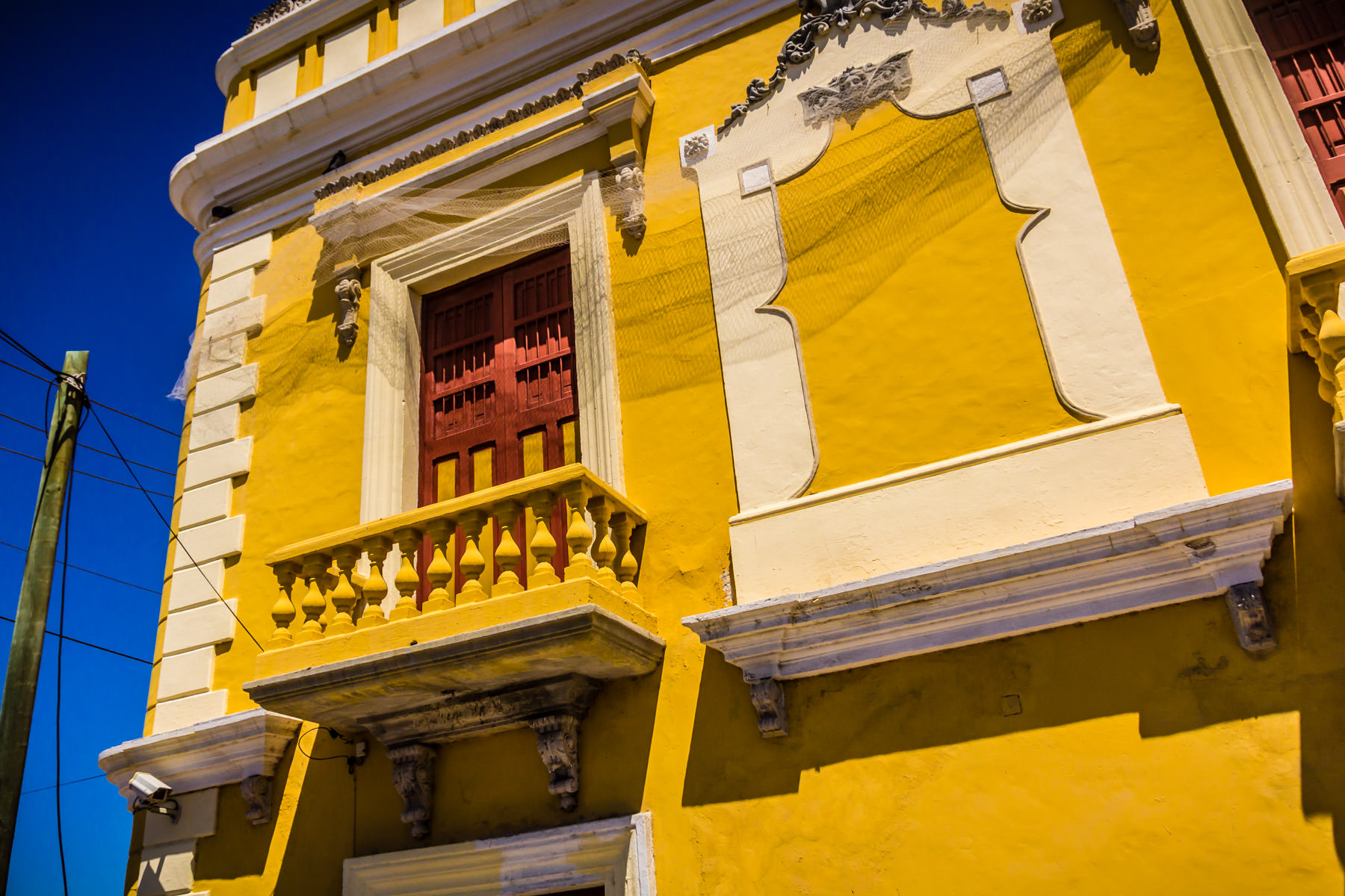 A red door on a balcony stands out against the yellow walls of its environs in Progreso de Mérida, Yucatan, Mexico.