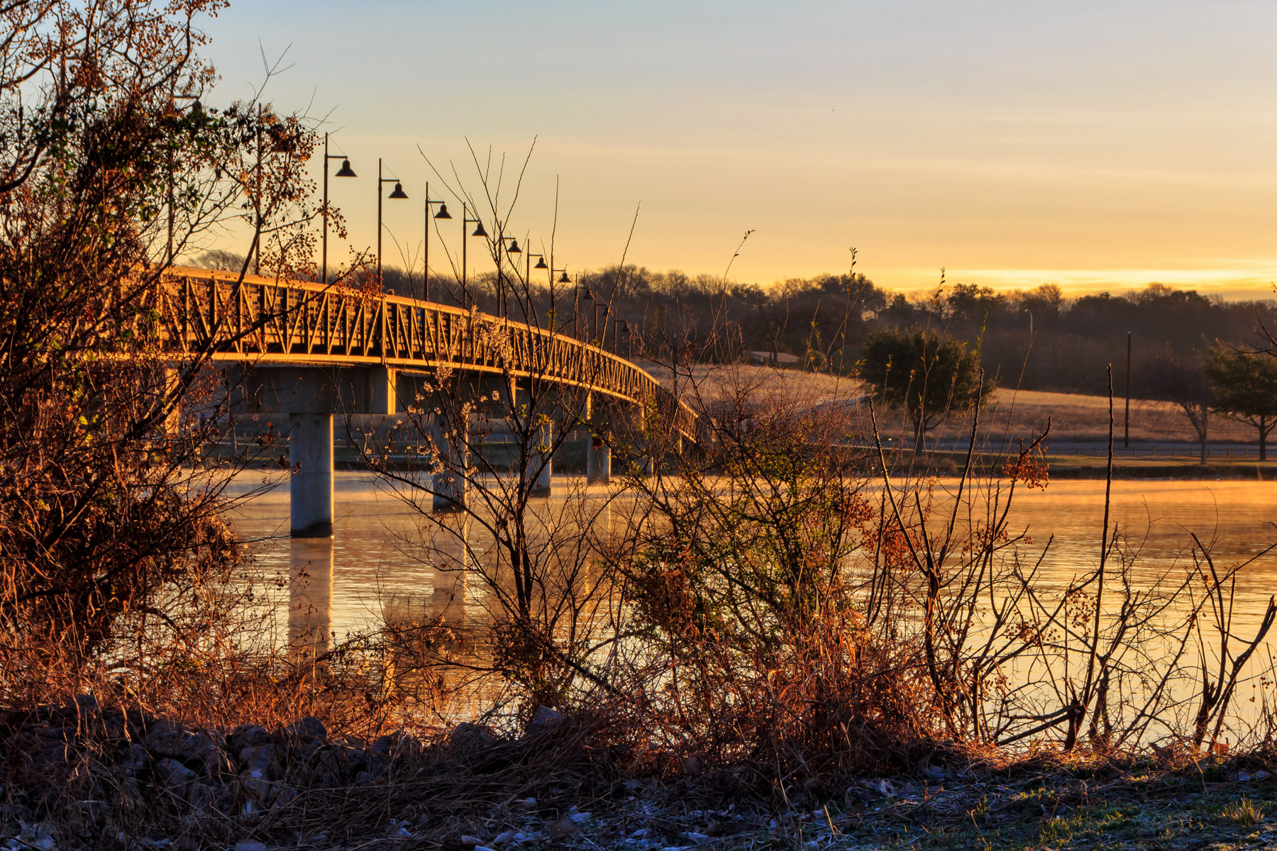 The golden light of the sun's first rays illuminates a footbridge over an inlet of Dallas' White Rock Lake.