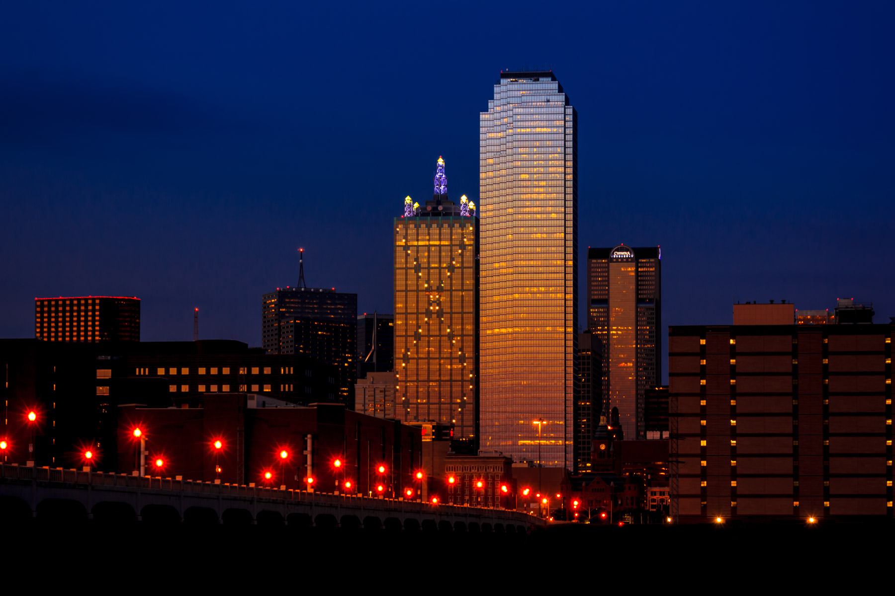 The last sunlight of the day splashes gold onto the West End of Downtown Dallas.