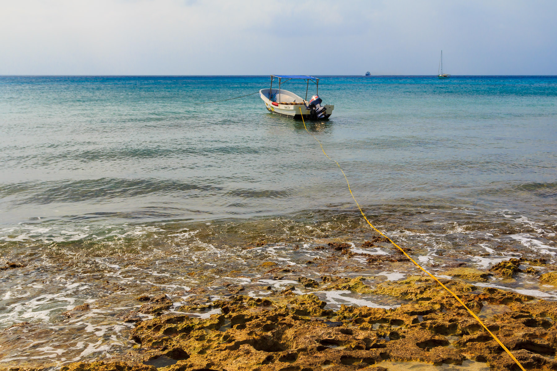 A boat tied to the shore along the waterfront of San Miguel, Cozumel, Mexico.