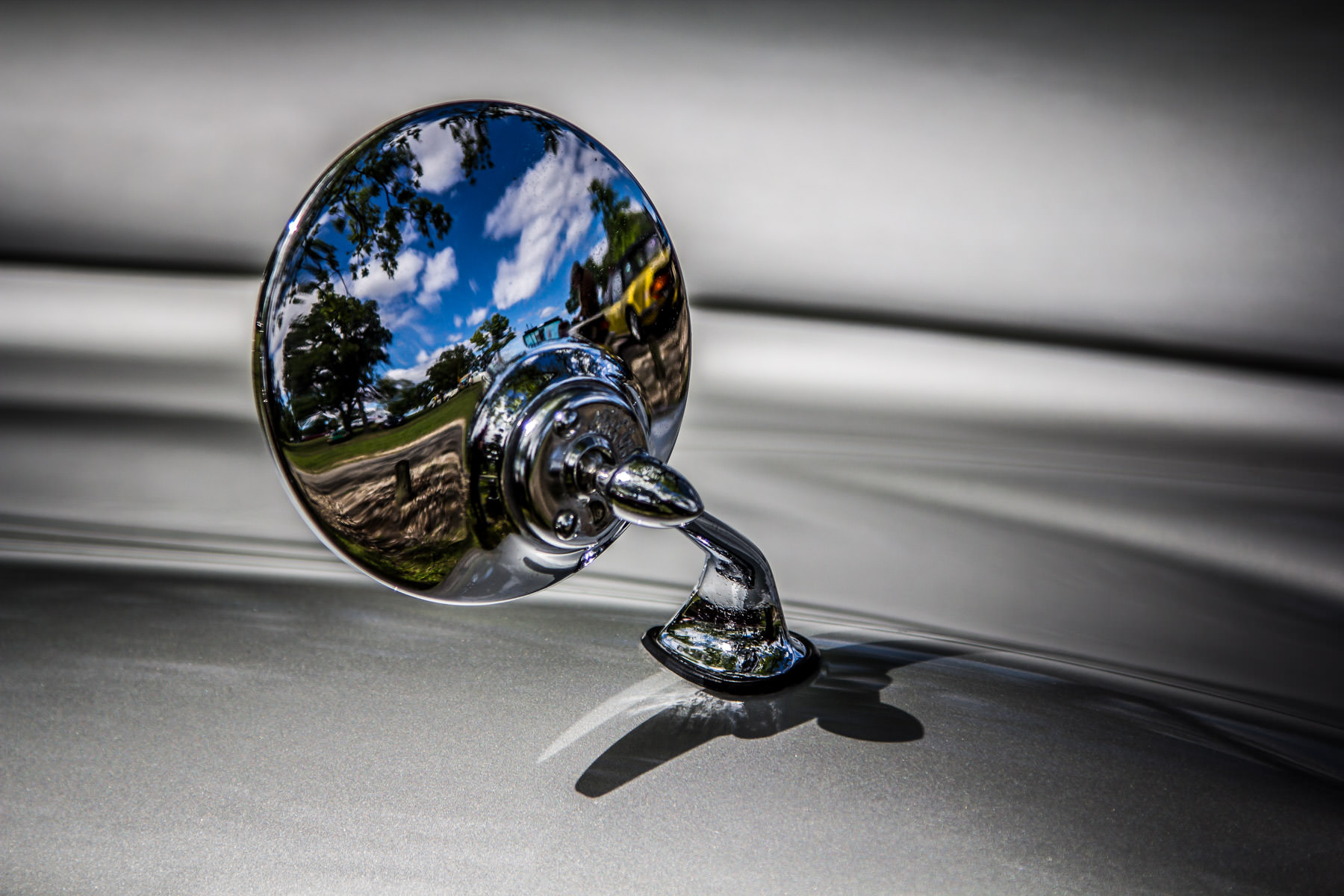 The wing mirror of a classic silver Jaguar at Dallas' All British and European Car Day.