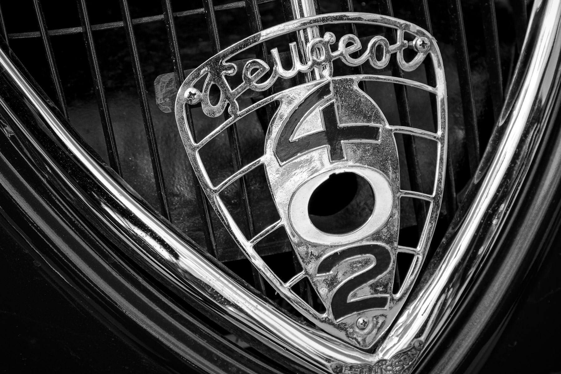 Detail of the grill badge of a classic Peugeot 402, spotted at Dallas' All British and European Car Day.