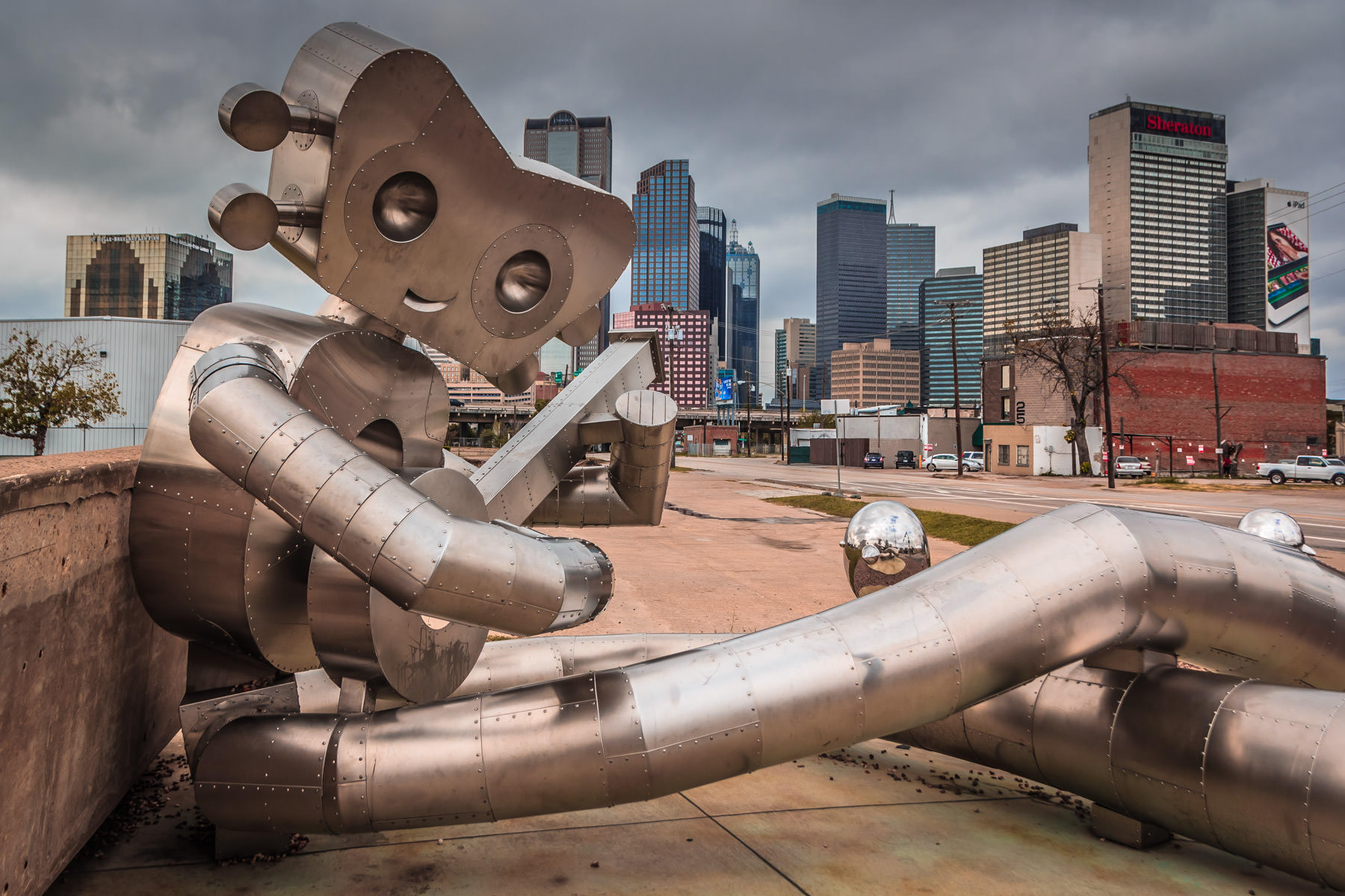 Dallas' Traveling Man sculpture—a landmark in the Deep Ellum neighborhood—against the city's downtown skyline.