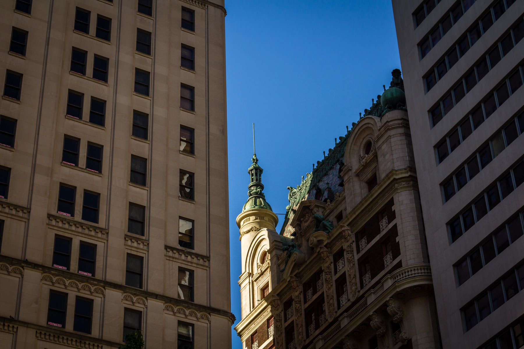 The spire atop Dallas' Adolphus Hotel rises into the sky, peeking out from the shadows of nearby buildings.