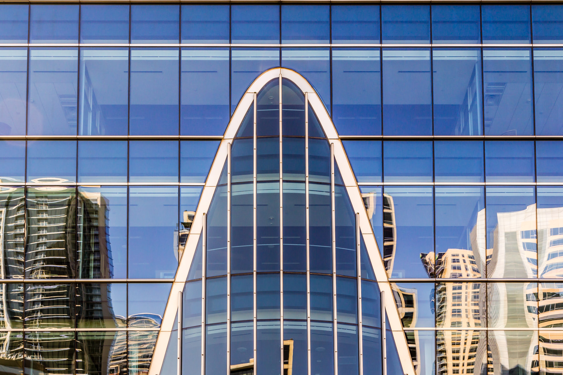 Uptown Dallas highrise buildings are reflected in this exterior detail of Downtown Dallas' Hunt Oil headquarters building.