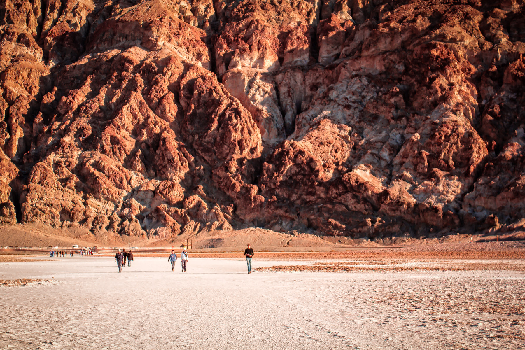 Visitors to Death Valley National Park's Badwater Basin—the lowest point in North America (282 ft or 86 m below sea level)—are dwarfed by the rocky face of an adjacent mountain.