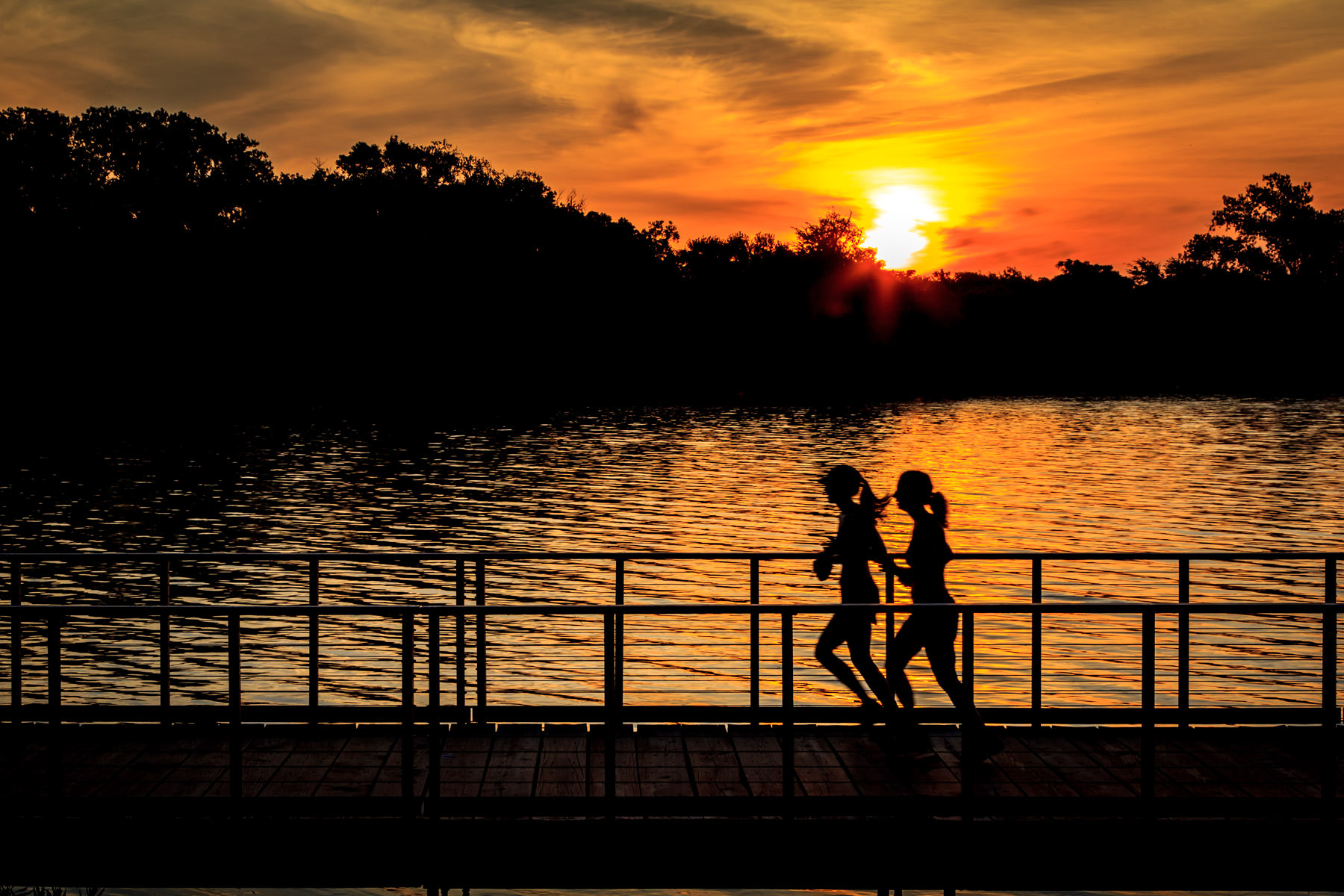 Joggers run along a footbridge as the sun rises over White Rock Lake, Dallas.