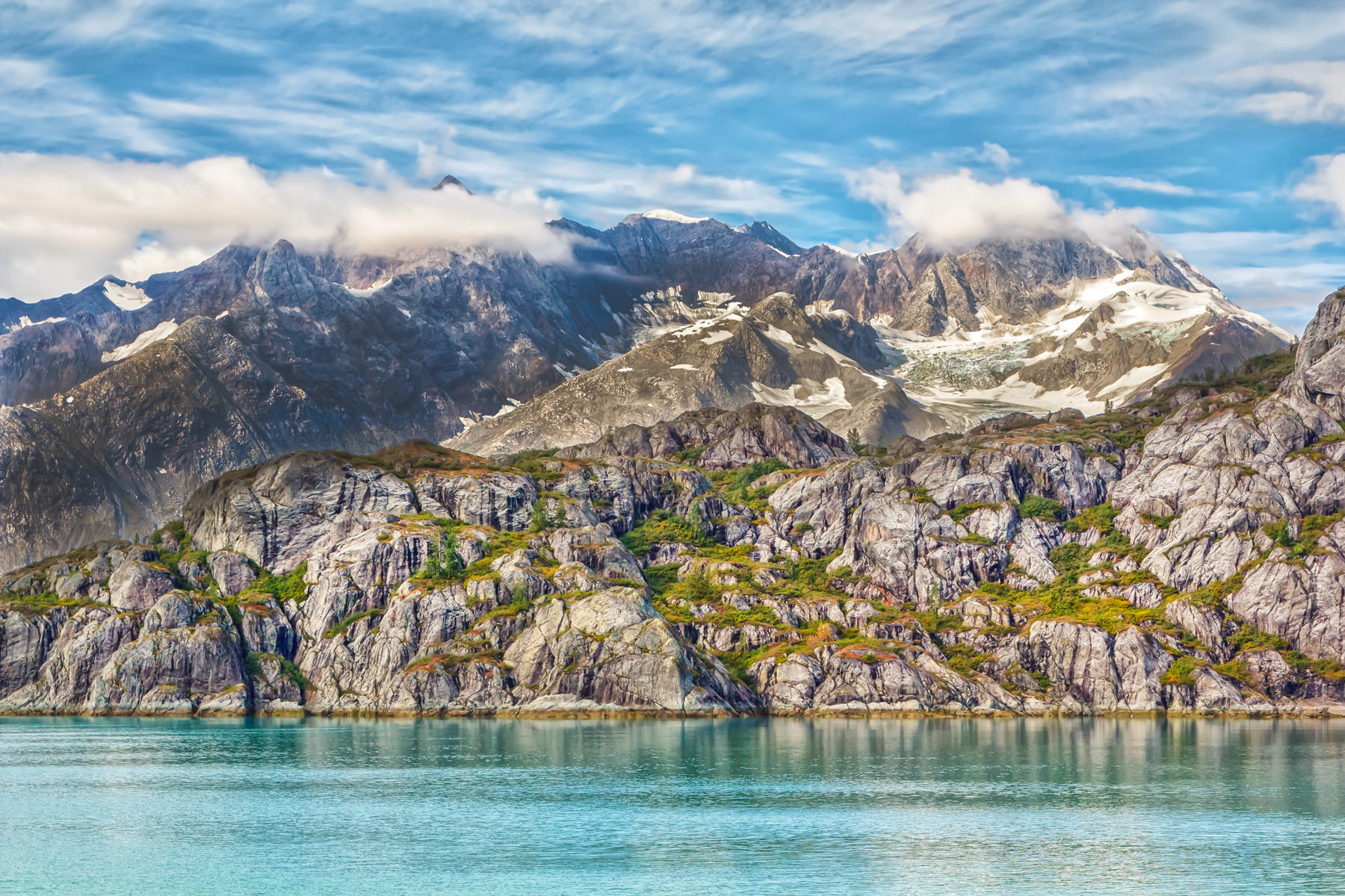 Jagged ice and snow-peaked mountains along the shores of Alaska's Glacier Bay National Park.