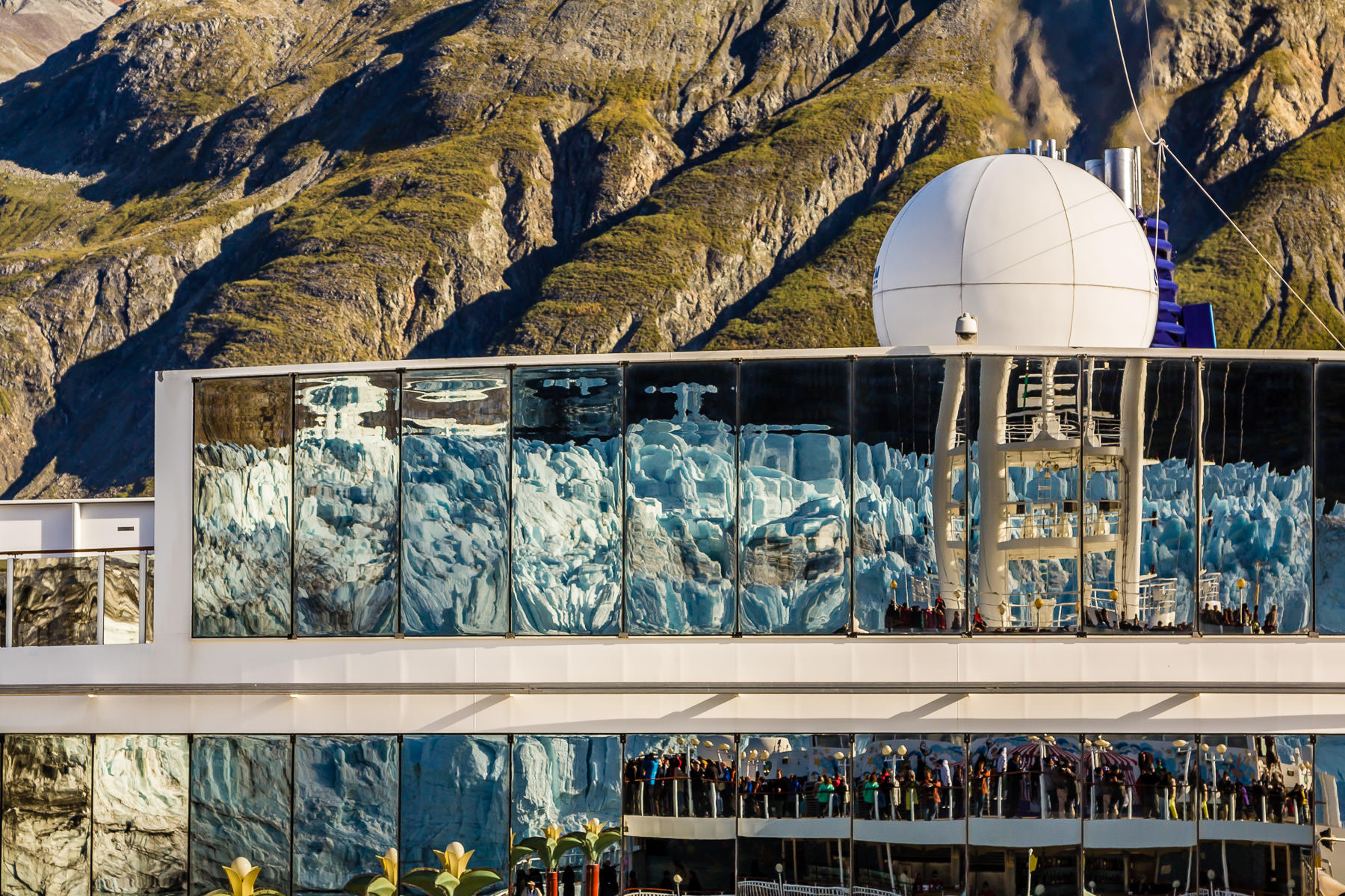 Alaska's Glacier Bay National Park's Margerie Glacier is reflected in windows aboard the cruise ship Norwegian Pearl.