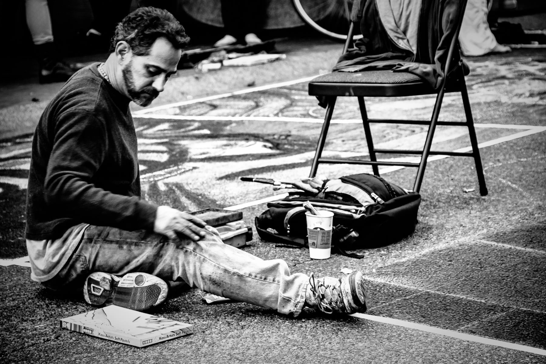 A chalk artist reaches for his medium at the 2013 Victoria International Chalk Art Festival, Victoria, British Columbia.