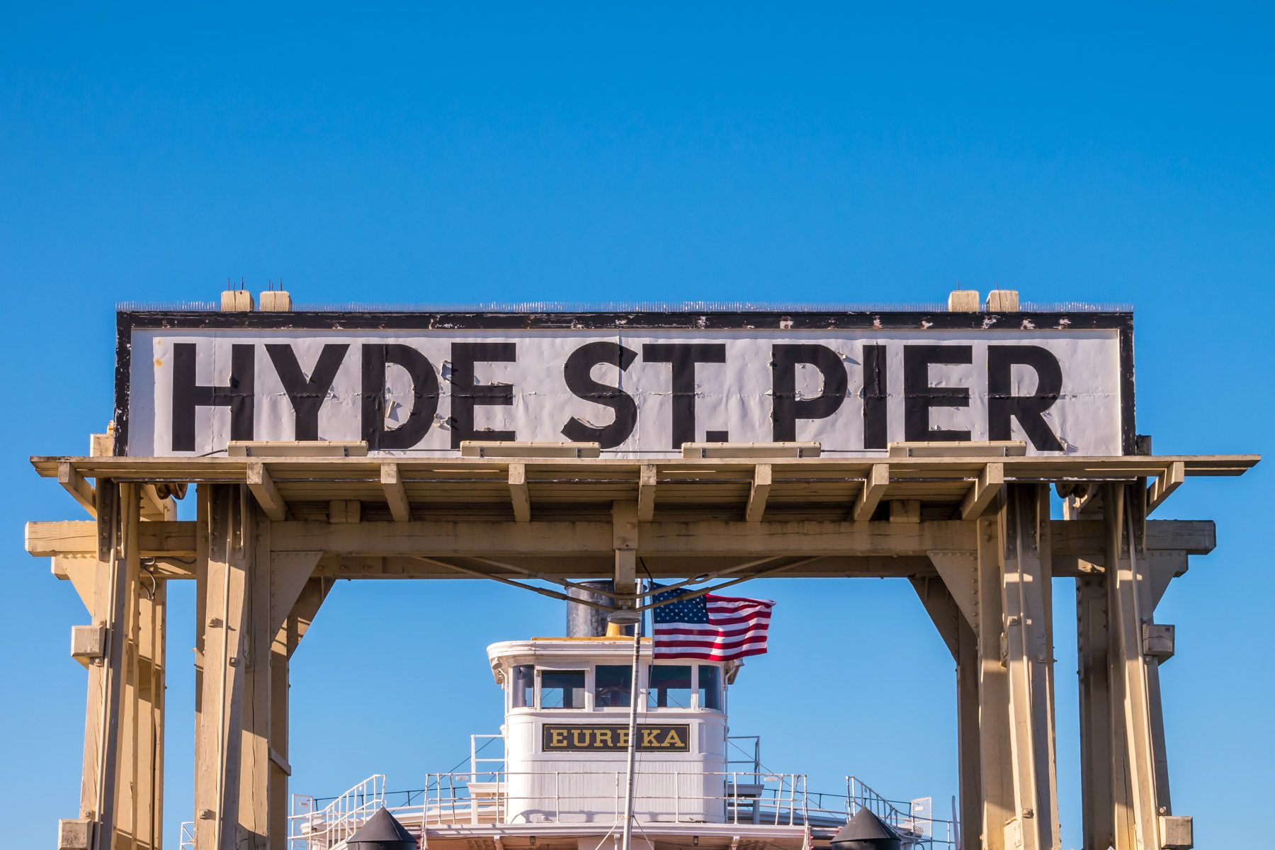 The bridge of the 1890 steam ferry Eureka peeks into the frame under the sign for the Hyde Street Pier at San Francisco's National Maritime Historical Park.