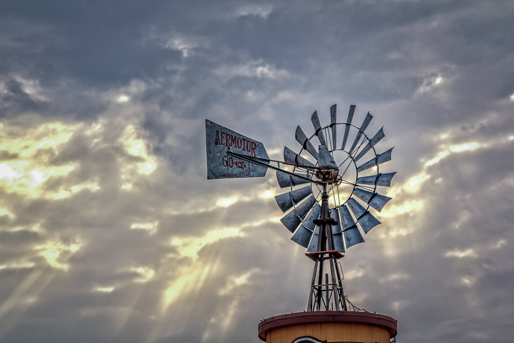 Sun rays pierce the clouds and illuminate a windmill in Downtown Grapevine, Texas.