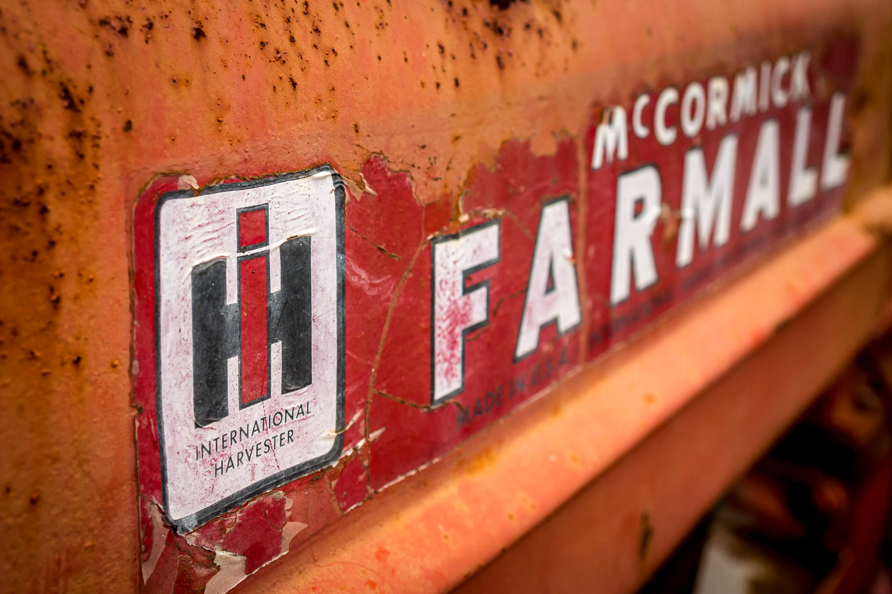 Detail of the cracked and peeling label of an International Harvester McCormick Farmall tractor, spotted at Moore Farms in Bullard, Texas.