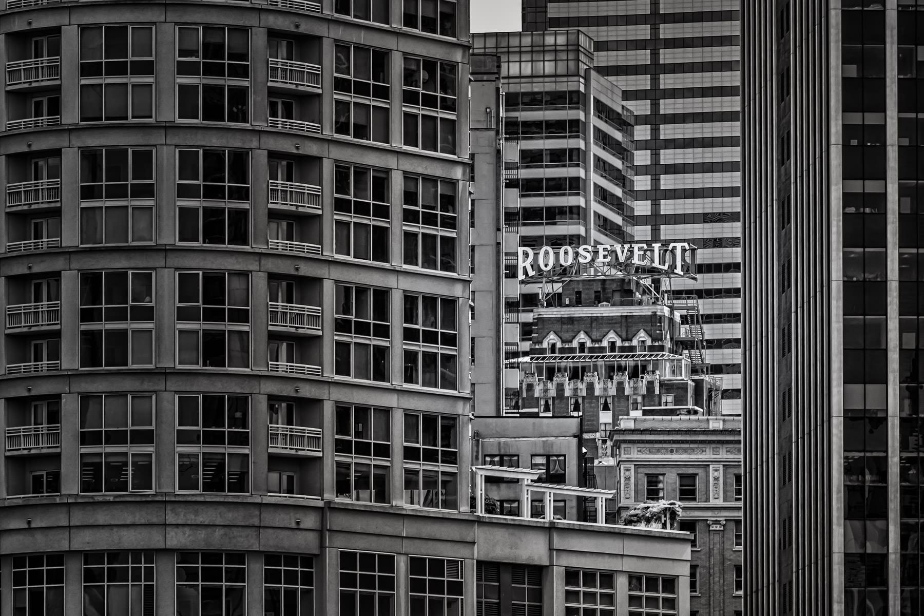The rooftop sign of Seattle's Roosevelt Hotel peeks through the surrounding buildings.