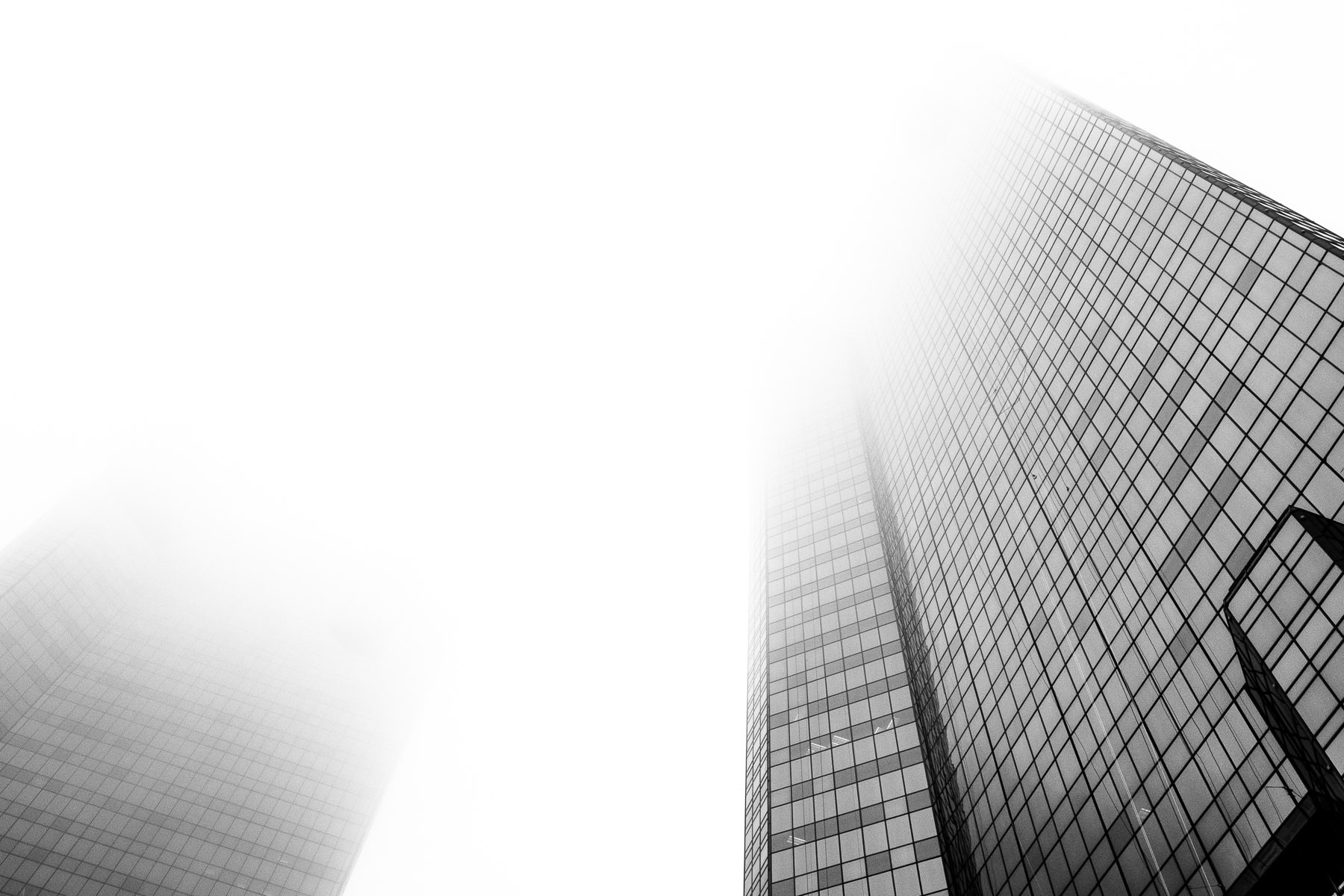 The two towers of the City Center Towers Complex—the D.R. Horton Tower and the Wells Fargo Tower—rise into the fog over Downtown Fort Worth, Texas.