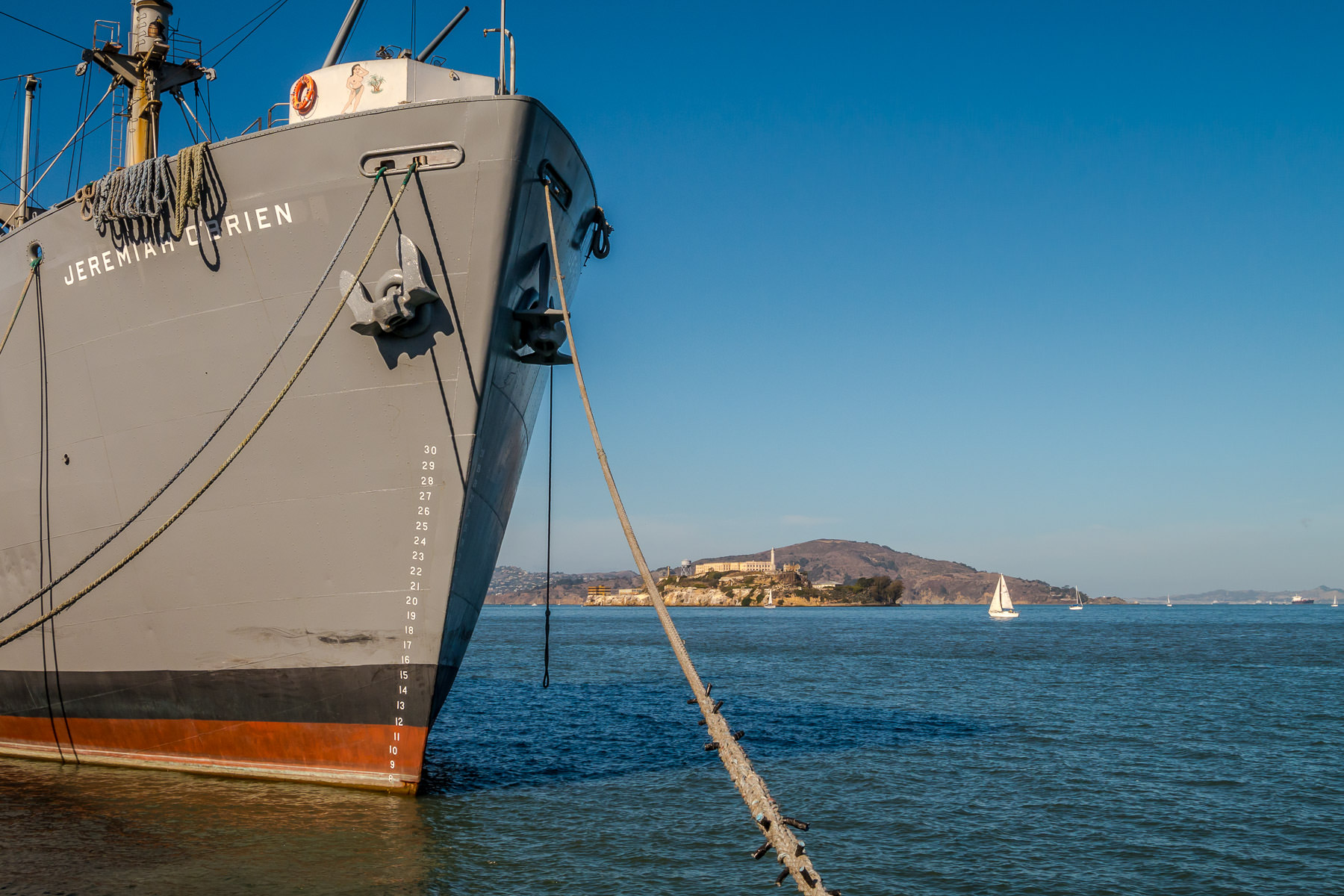 The bow of the SS Jeremiah O'Brien—one of only two surviving operational Liberty ships from World War II—docked at San Francisco's Pier 45 with Alcatraz Island as its backdrop.