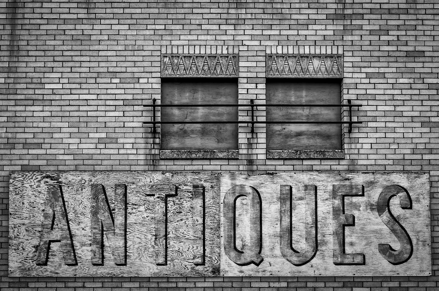 A fading plywood sign advertising an antiques shop in the East Texas town of Gladewater.