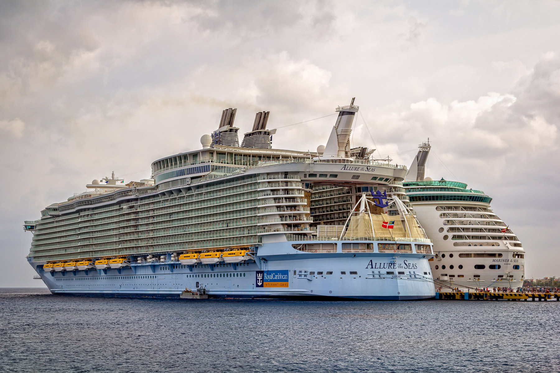 The Royal Caribbean cruise ships Allure of the Seas and Mariner of the Seas docked at Cozumel, Mexico on an overcast day.