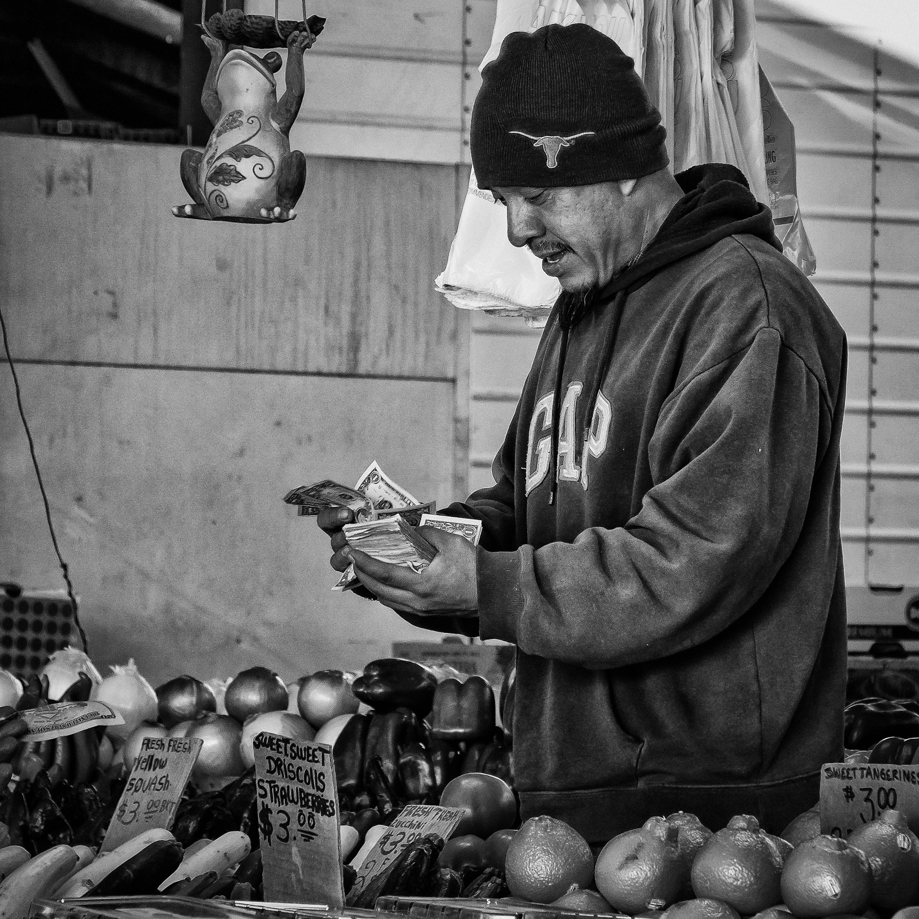 A vendor at the Dallas Farmers Market counts money during a lull in business on a cold winter morning.