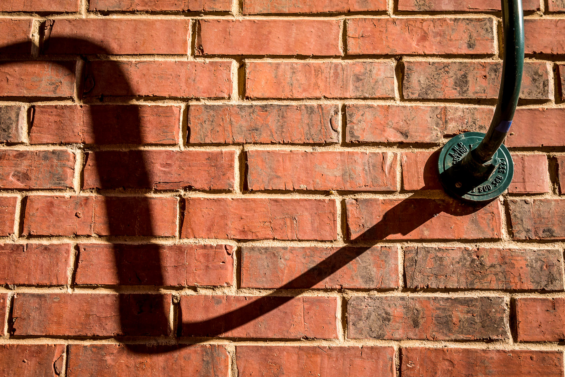 A lamp throws a shadow onto a brick wall at Eastside Village in Downtown Plano, Texas.