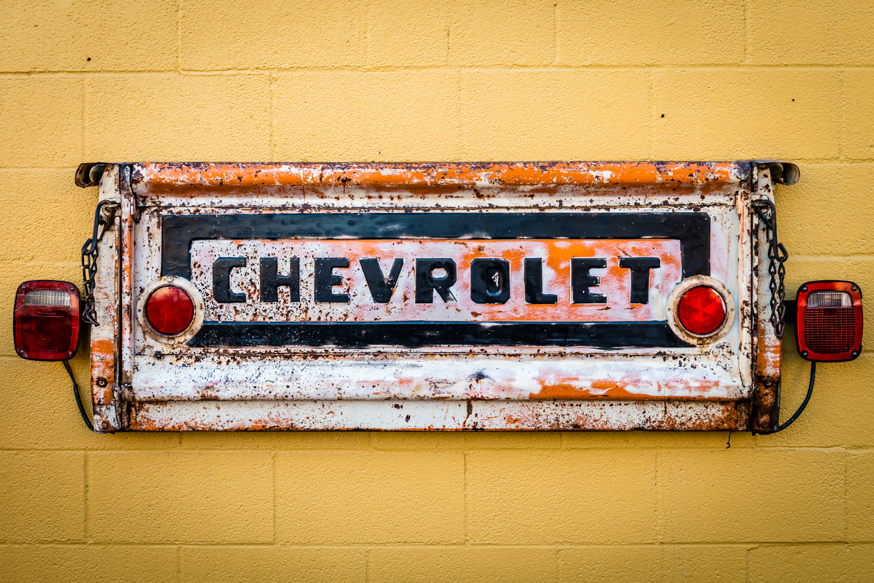 A tailgate from an old Chevrolet pickup truck mounted on a wall as part of the exterior decor of Cajun Tailgators restaurant in Downtown Plano, Texas.