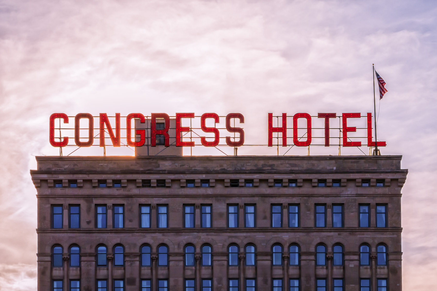 """The sun begins to set behind Chicago's """"most-haunted"""" hotel, the Congress Plaza Hotel, highlighting its rooftop's red neon sign and American flag."""