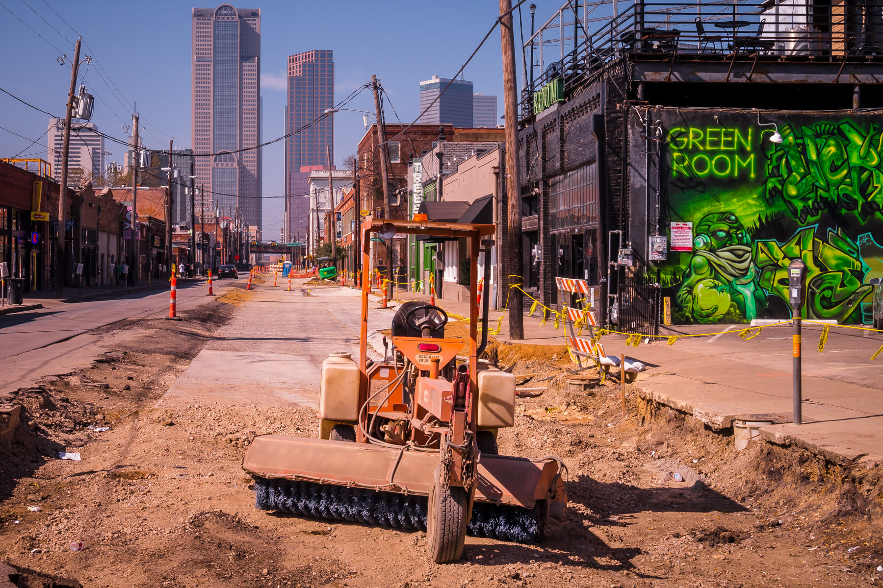 Downtown Dallas rises at the far end of the temporarily under-construction Elm Street in the Deep Ellum neighborhood.