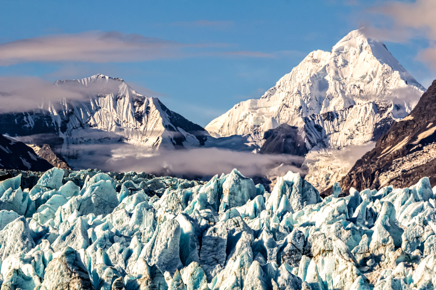 Rugged, snow-capped mountains rise beyond Alaska's Margerie Glacier at Glacier Bay National Park.