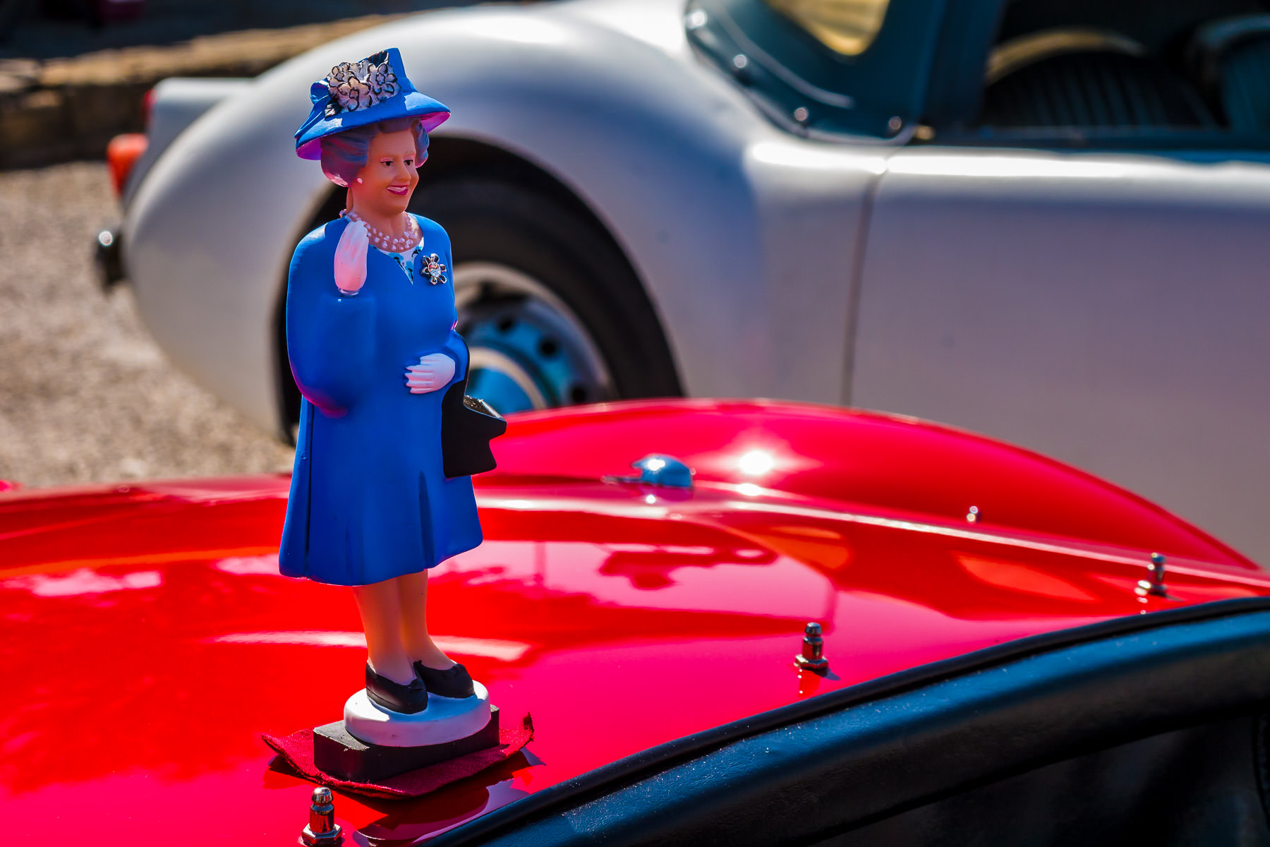 A figurine of Queen Elizabeth sits atop the boot lid of an MG at Dallas' All British and European Car Day.
