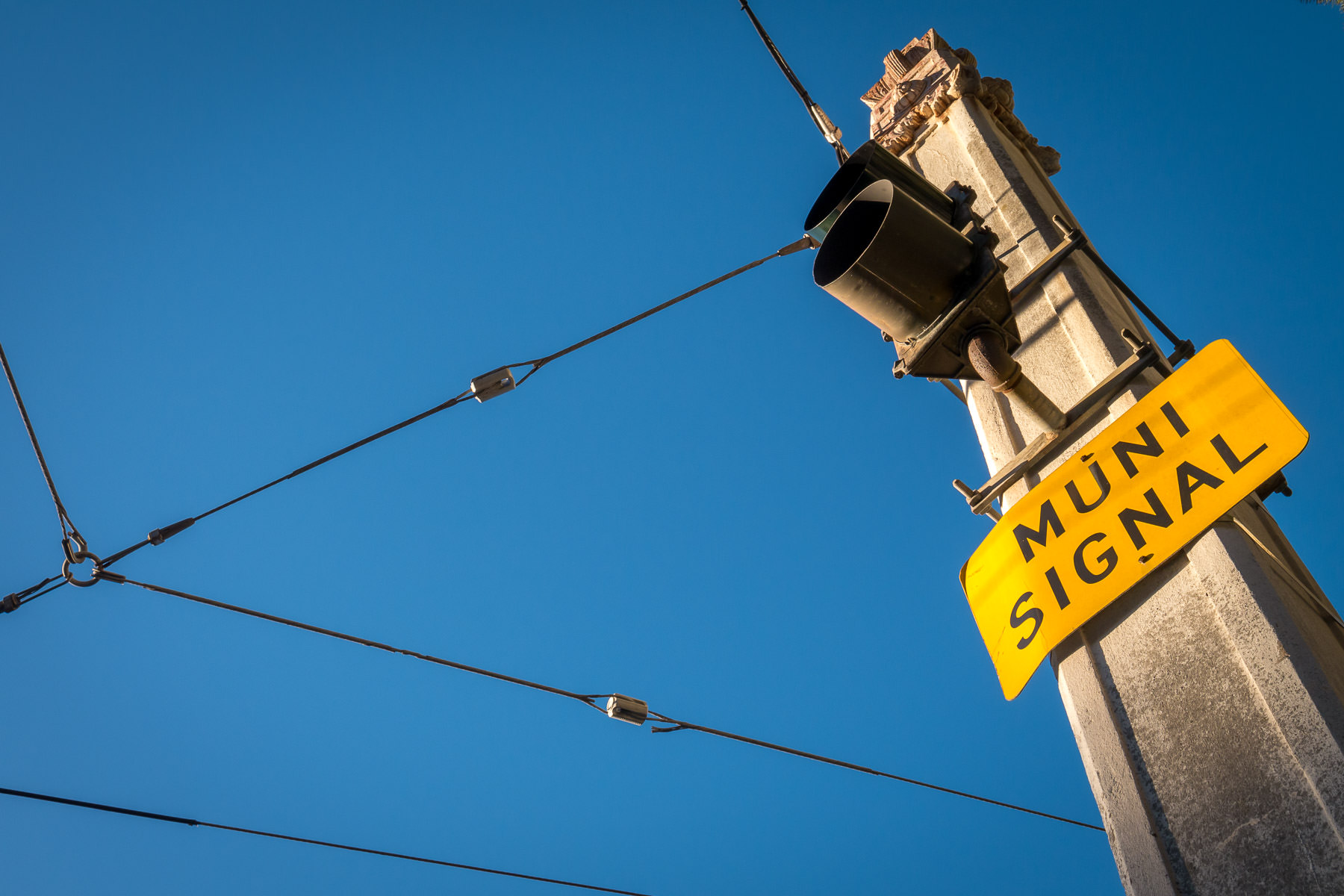 A street pole supporting overhead wires for trolley buses operated by San Francisco's public transit agency, Muni.