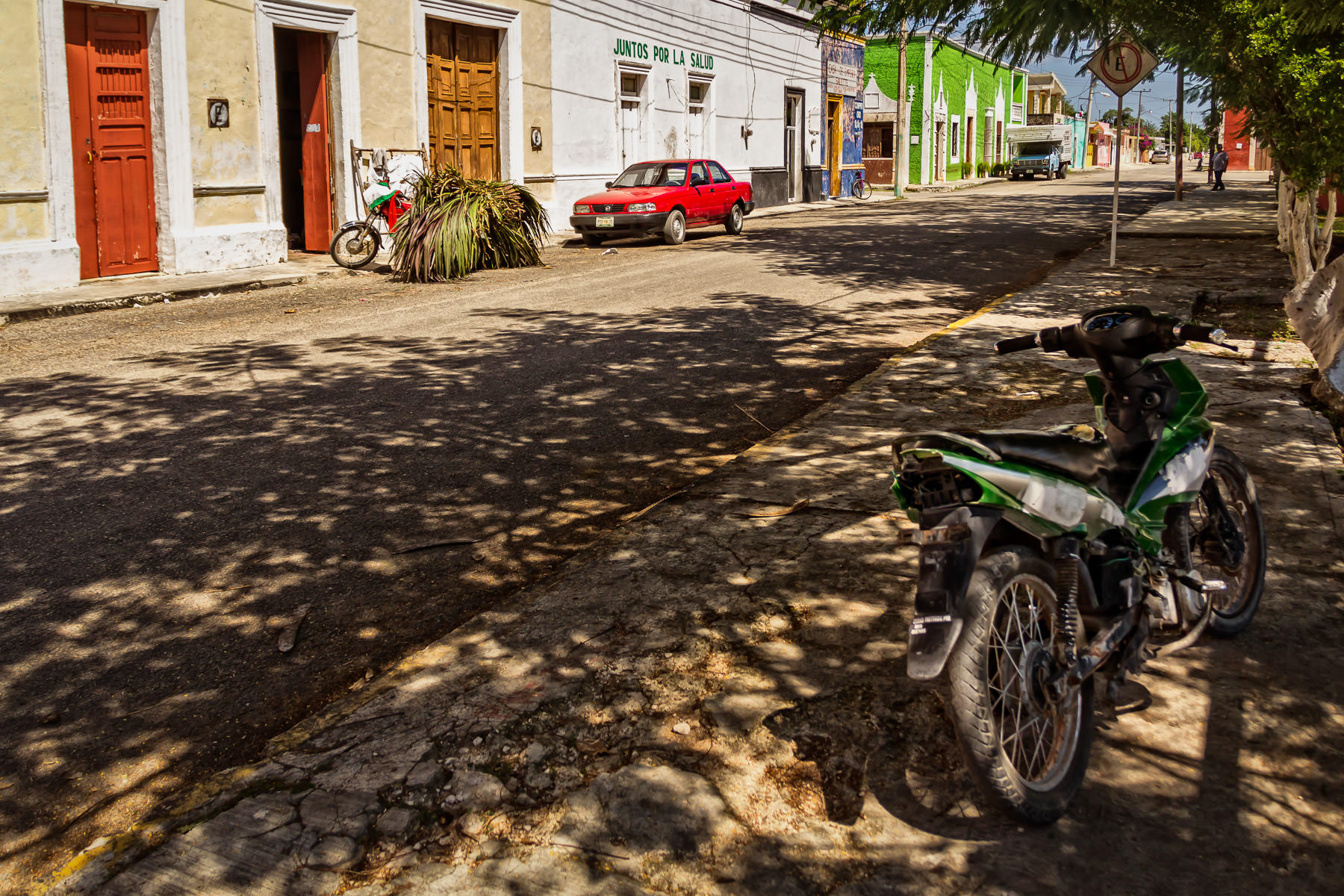 A motorcycle sits in the shade on a street in the village of Dzemul, Yucatan, Mexico.