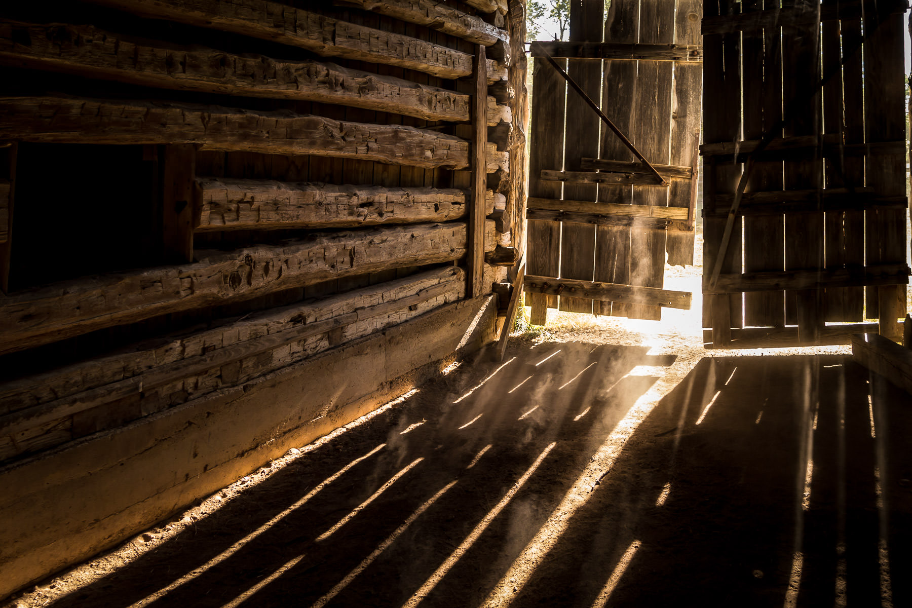 Sun rays spill through the cracks of a door on a dilapidated barn at Penn Farm, Cedar Hill State Park, Texas.
