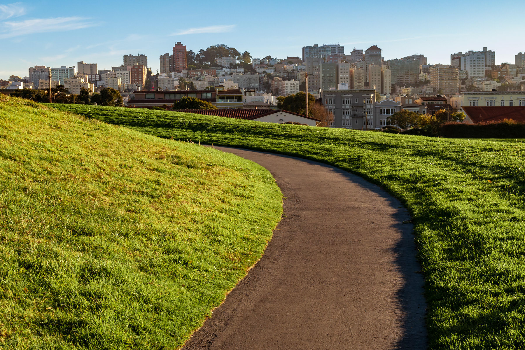 A path crests a hill in the Great Meadow at Fort Mason as the late afternoon sun begins to set on San Francisco.