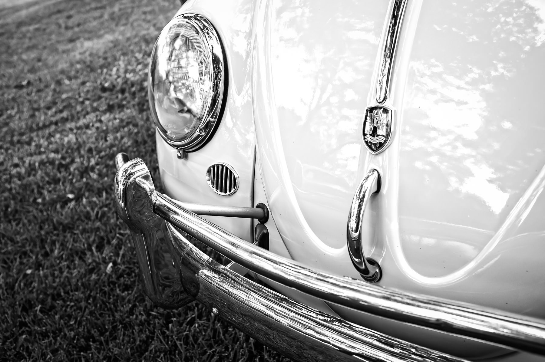 The right headlight of a classic Volkswagen Beetle at Dallas' Autos in the Park car show at Cooper Aerobics Center.