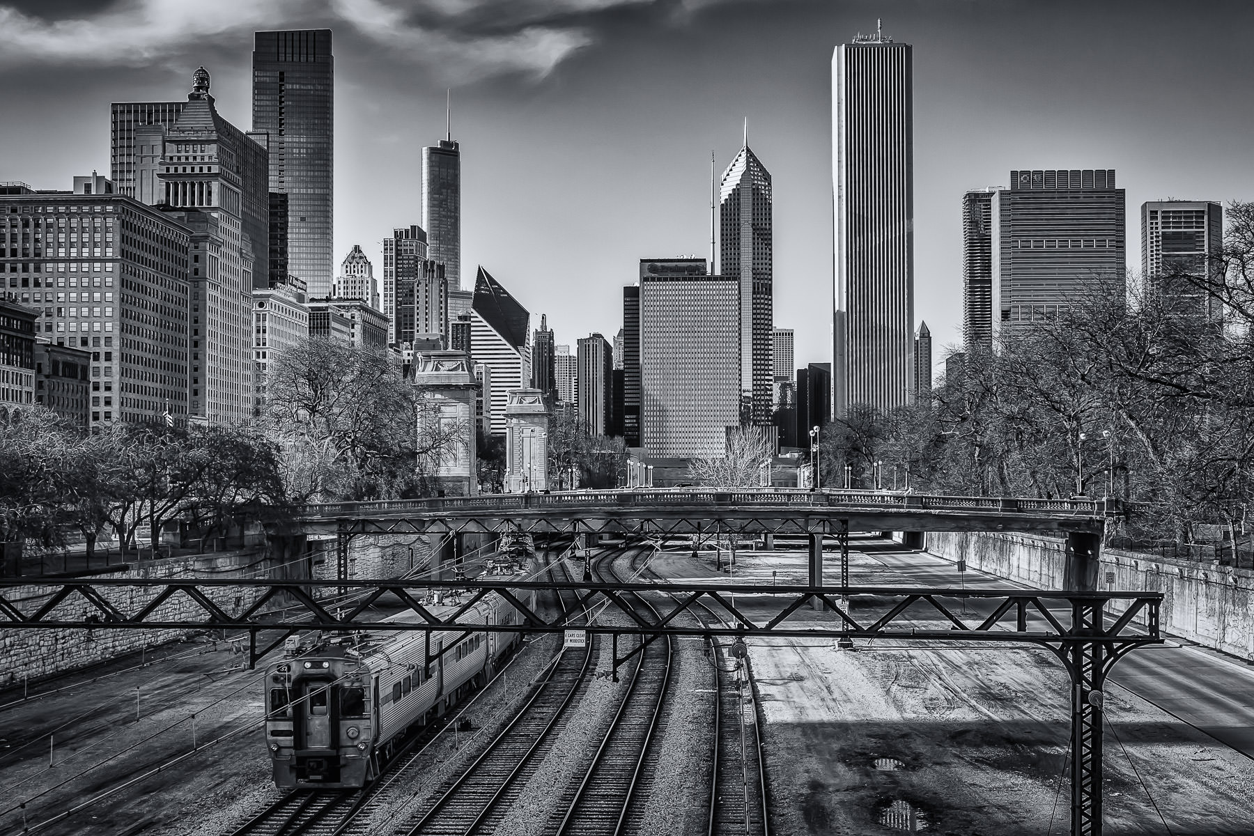 The Metra Electric and South Shore Line tracks pass through Chicago's Grant Park as the city's skyline rises in the distance.