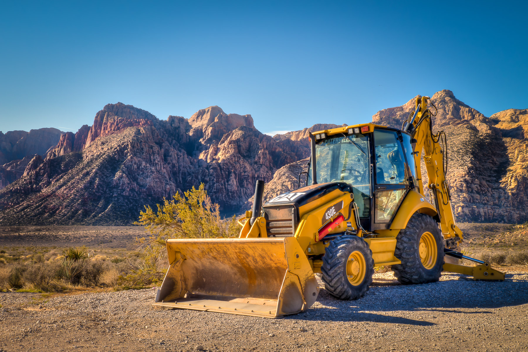 A front-end loader sits in the Nevada sun at Red Rock Canyon.