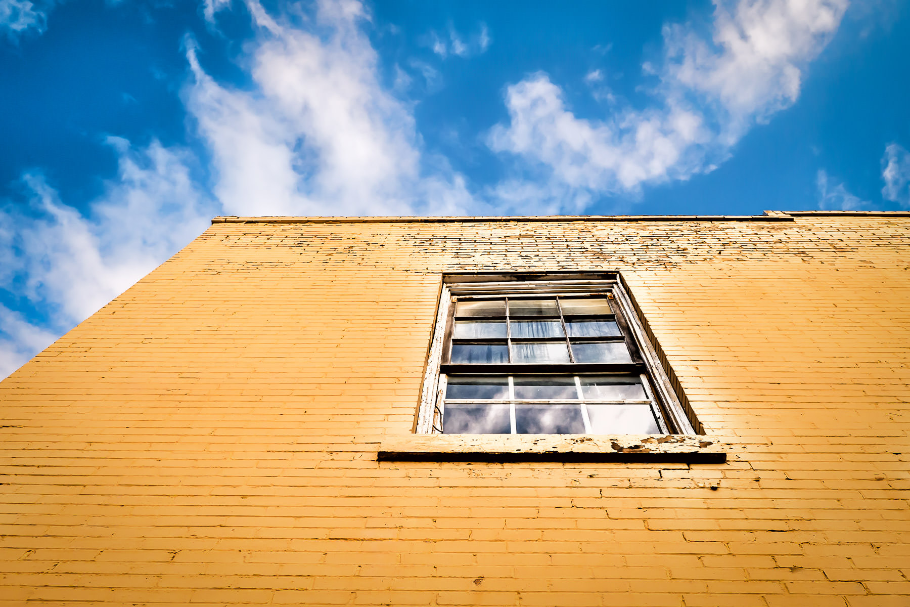 A window on a yellow-bricked building rises into the Texas sky in Downtown Waxahachie.