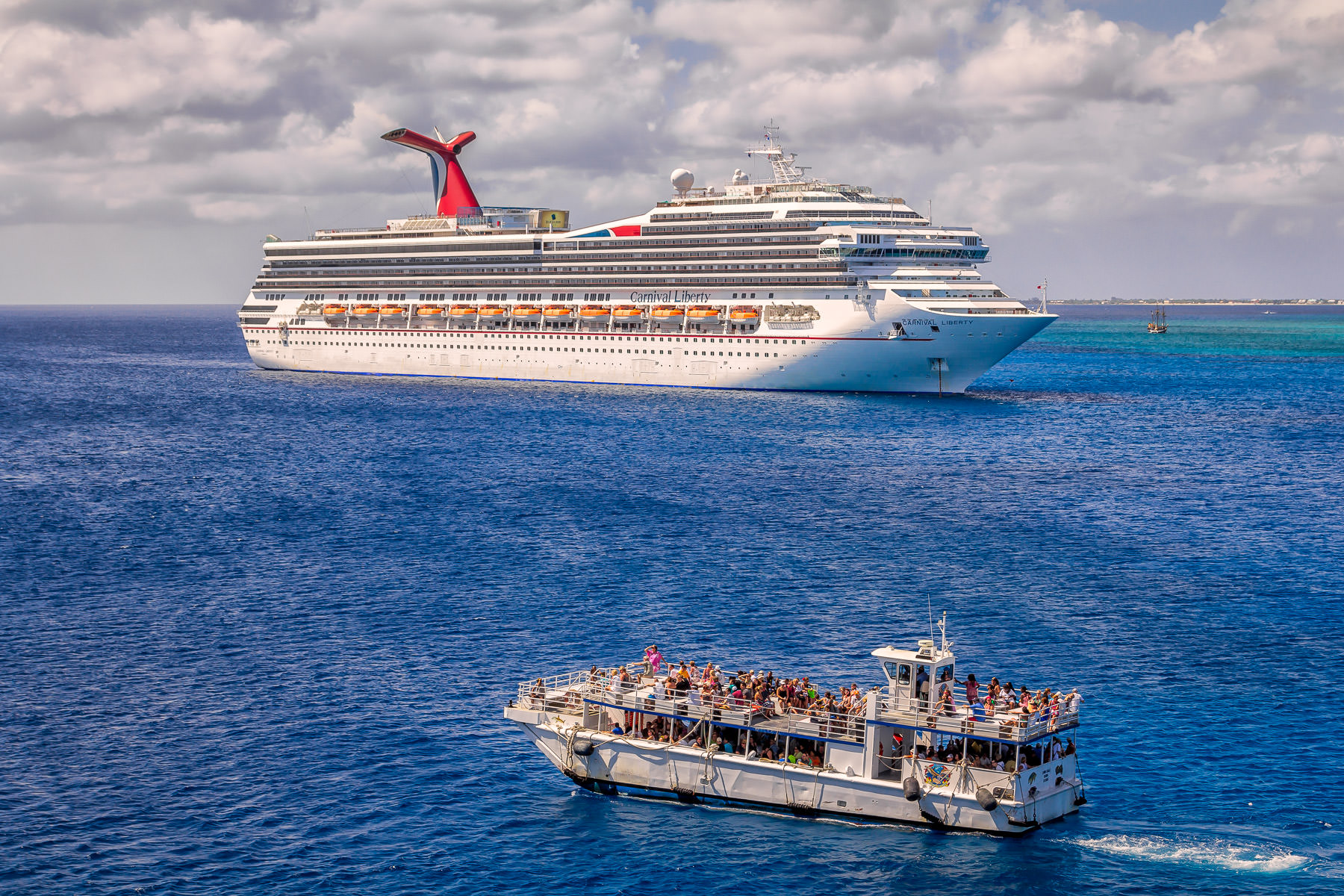 A cruise ship tender—used to transport passengers between a port and a ship when the ship is unable to dock directly due to shallow water or other reasons—passes the Carnival Liberty just off the coast of George Town, Grand Cayman.