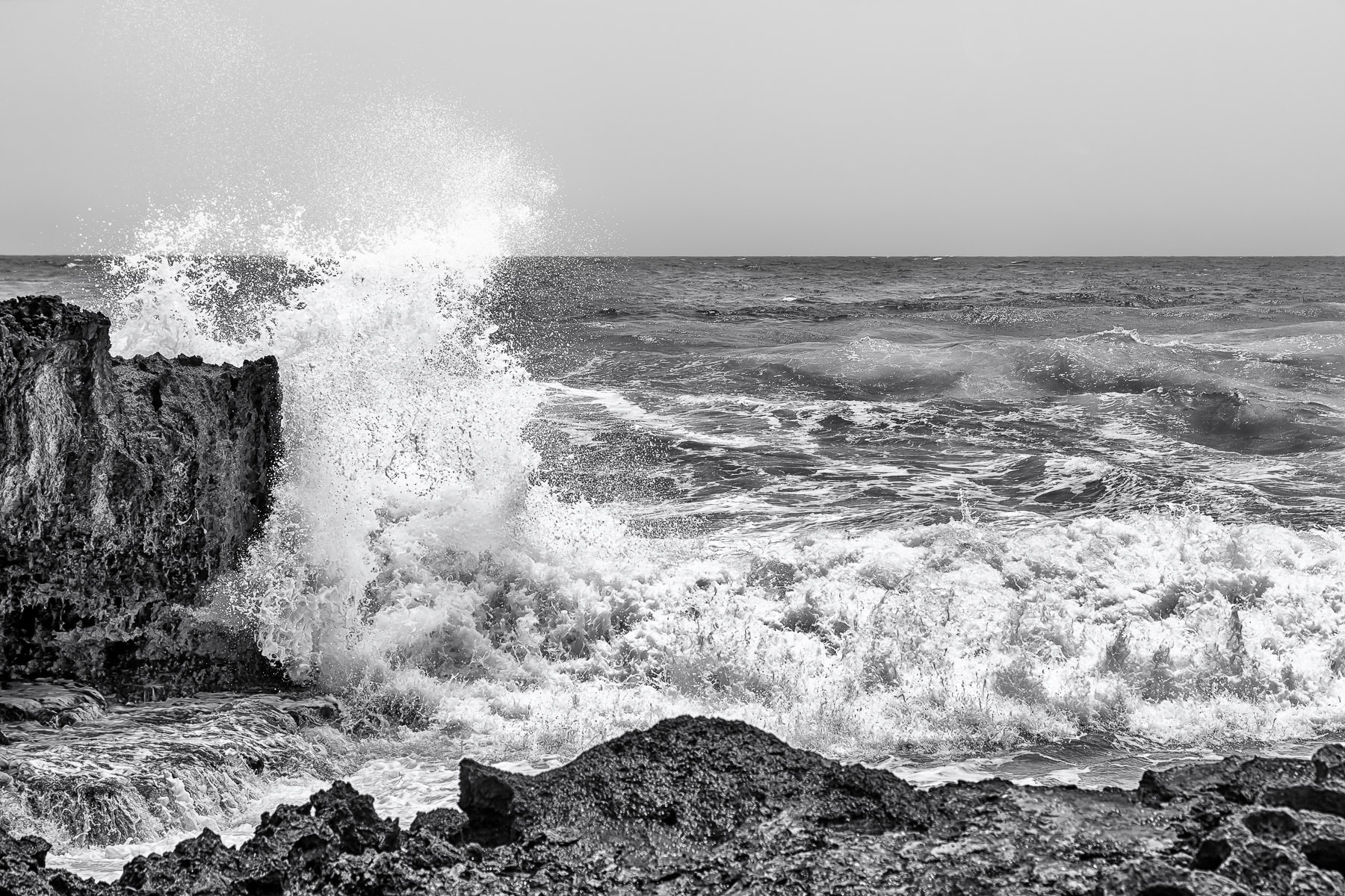 The roiling waves of the Atlantic Ocean splash onto the rocky shoreline of southeast Cozumel, Mexico.