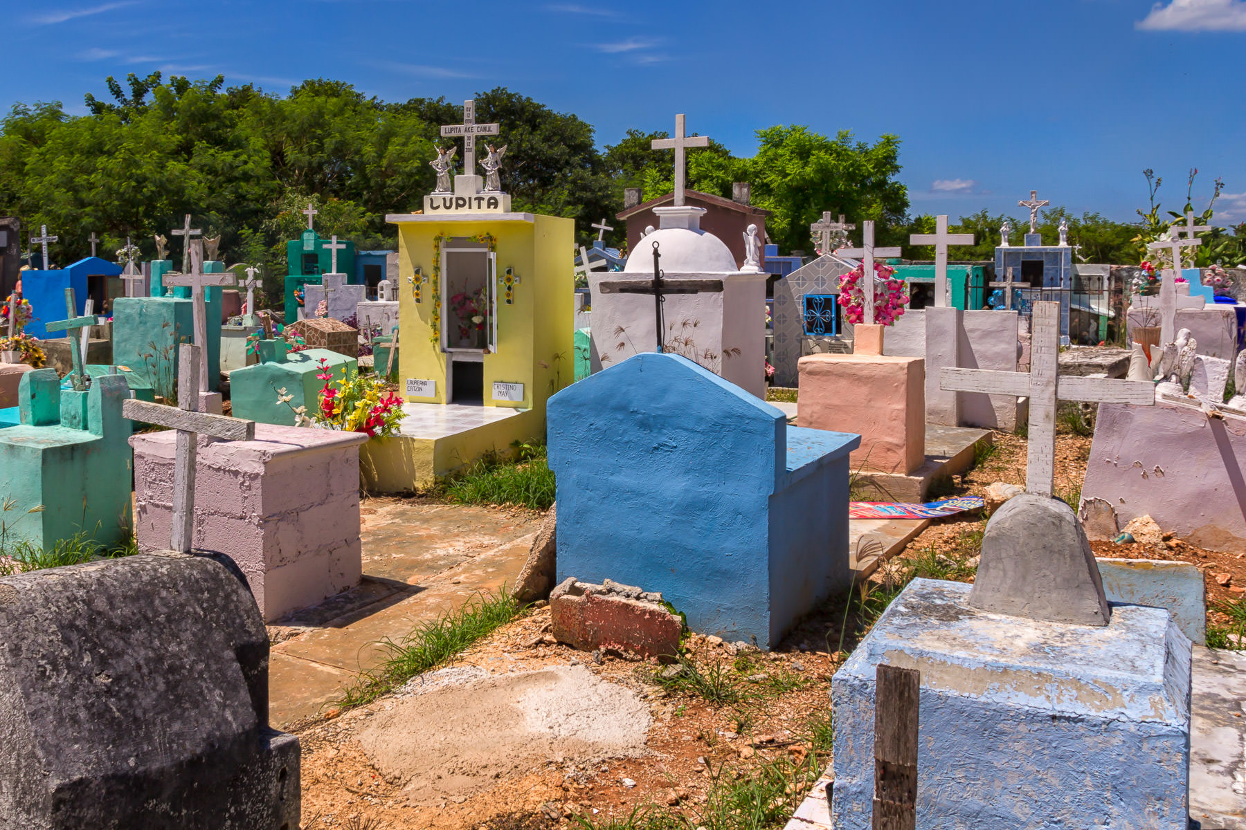 Simple, colorful graves in a cemetery in the small village of Dzemul, Yucatan, Mexico.