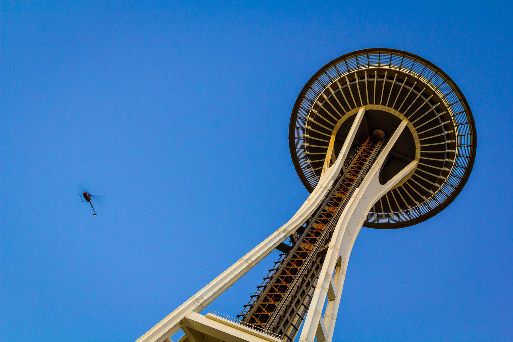 A helicopter flies past Seattle's Space Needle on a clear late-summer evening.
