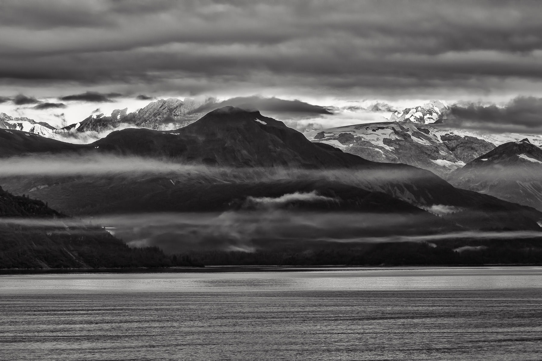 Wispy clouds hover around mountains rising from Alaska's Glacier Bay.