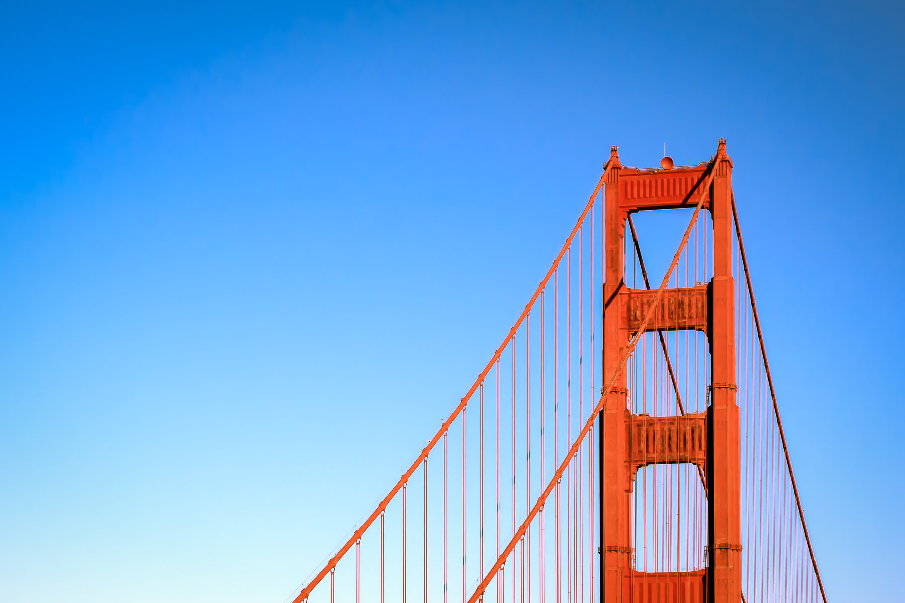 The south tower of San Francisco's iconic Golden Gate Bridge rises into the blue sky over San Francisco Bay.