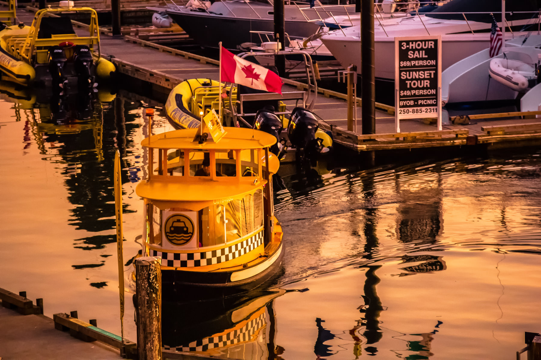 A water taxi glides between piers as the sun sets on Victoria, British Columbia's Inner Harbour.