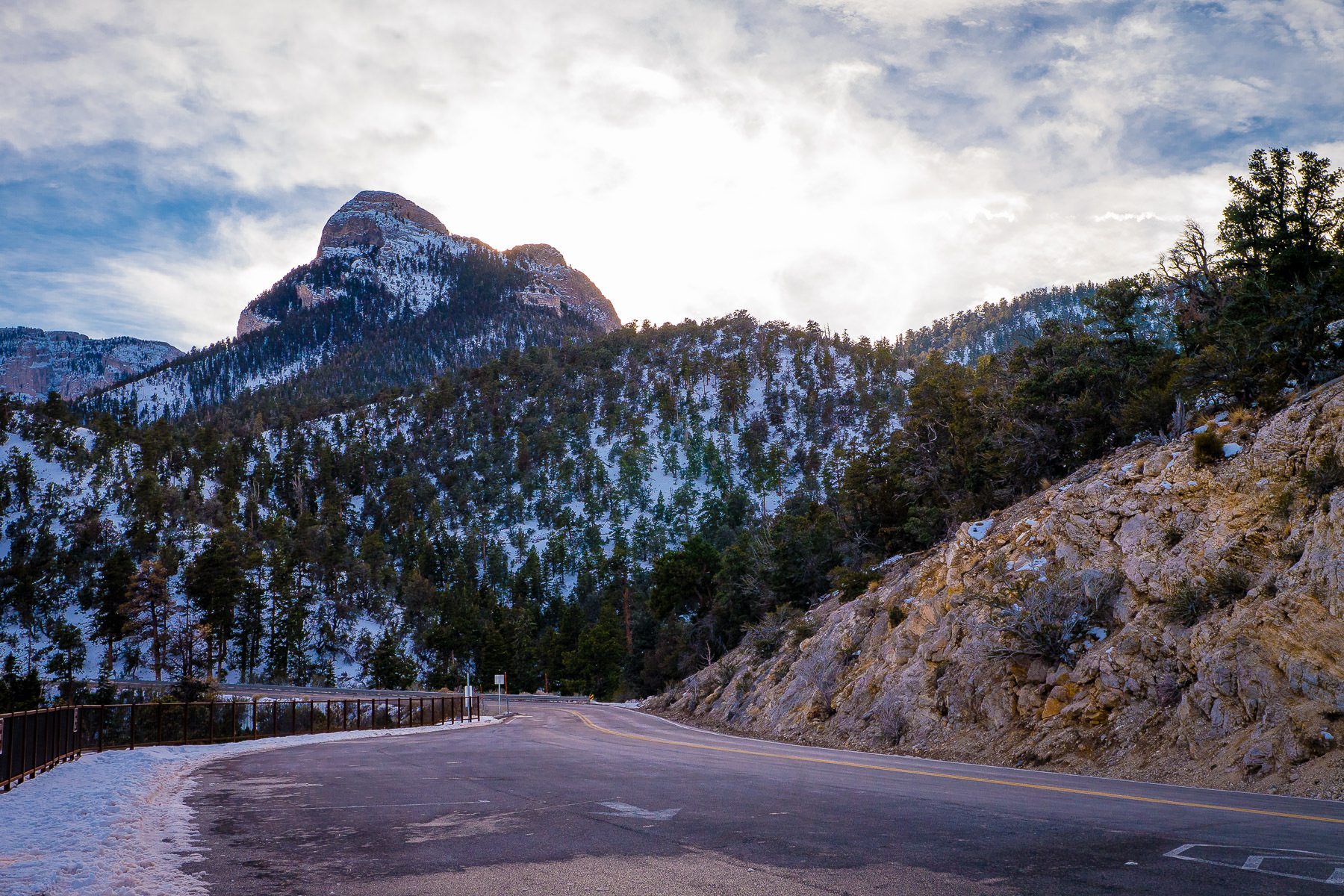 State Route 158 winds its way through snow-covered foothills as the sun begins to set behind Nevada's Mount Charleston.