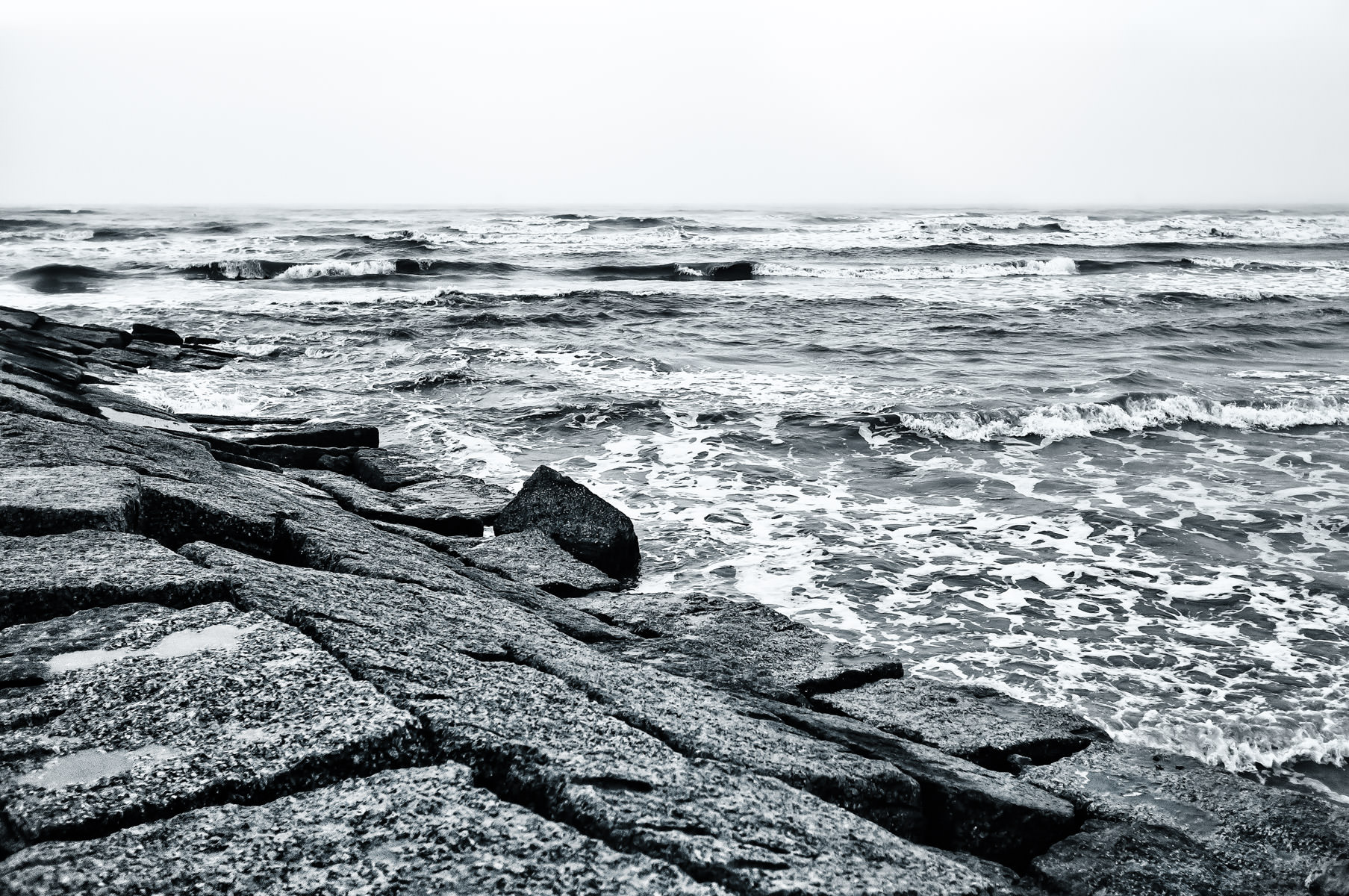 Waves crash against a granite groyne on an overcast day at Galveston Island, Texas.
